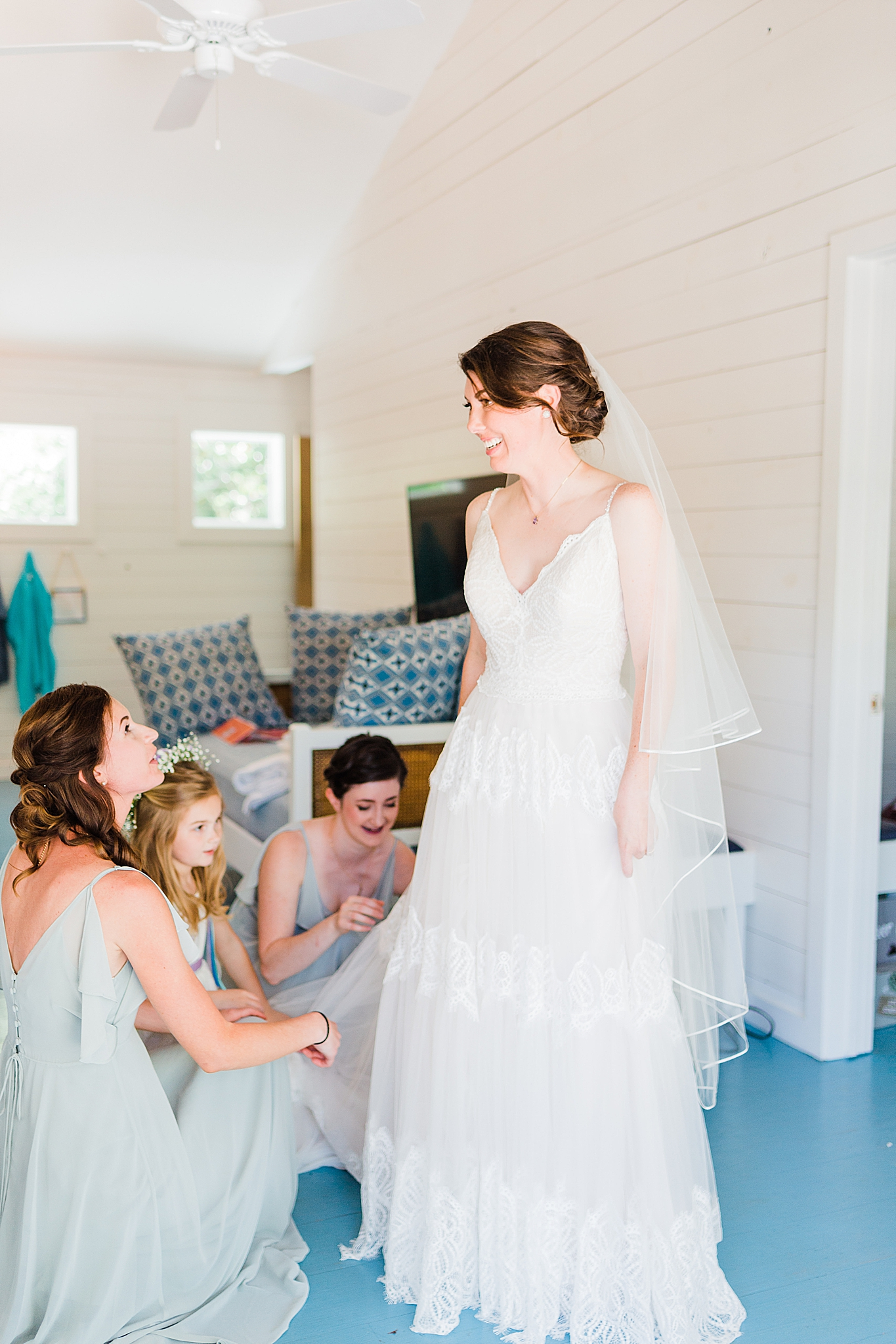 bridesmaids help bride with wedding gown