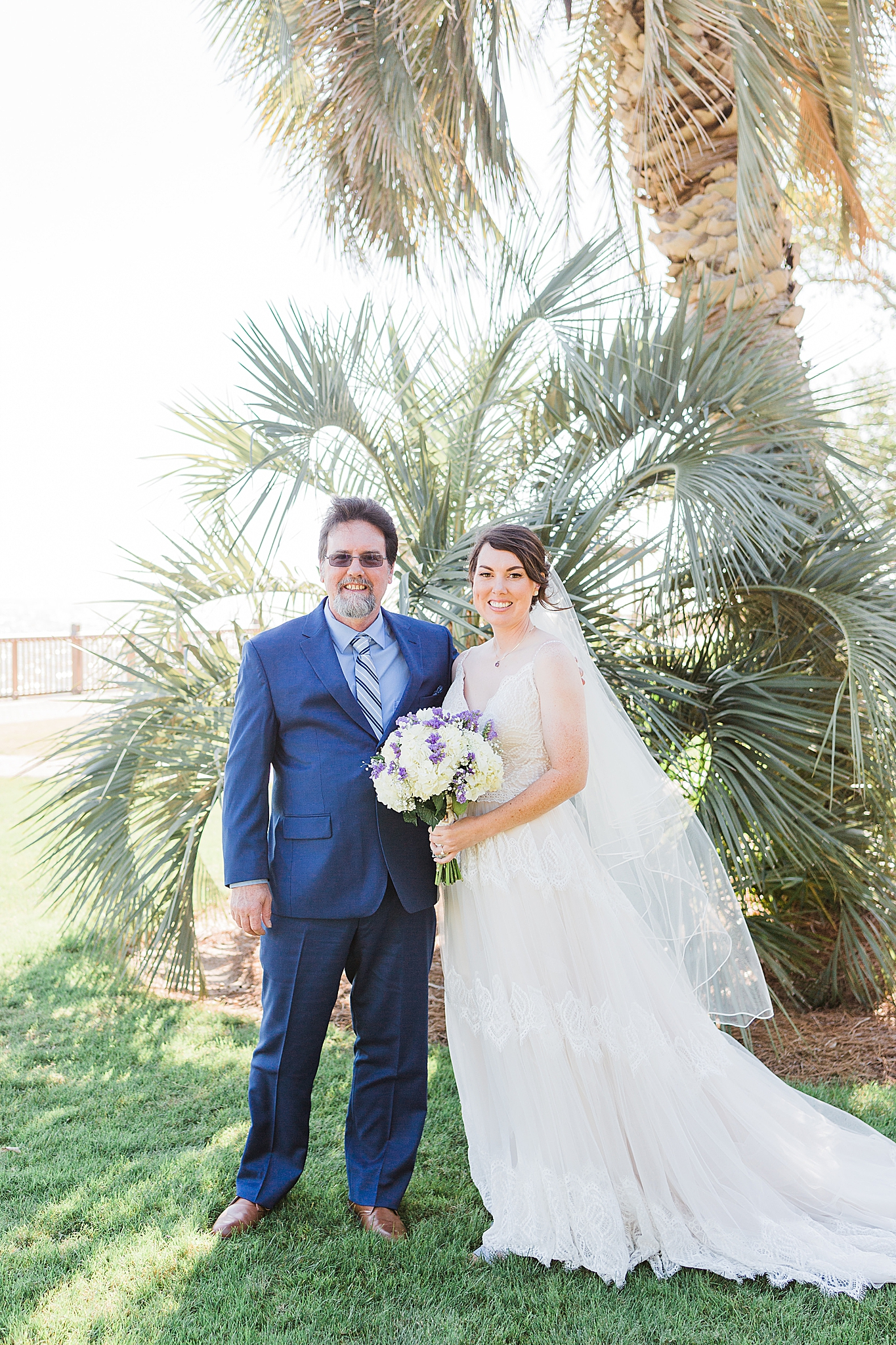 bride and dad pose by palm tree in Fairhope AL