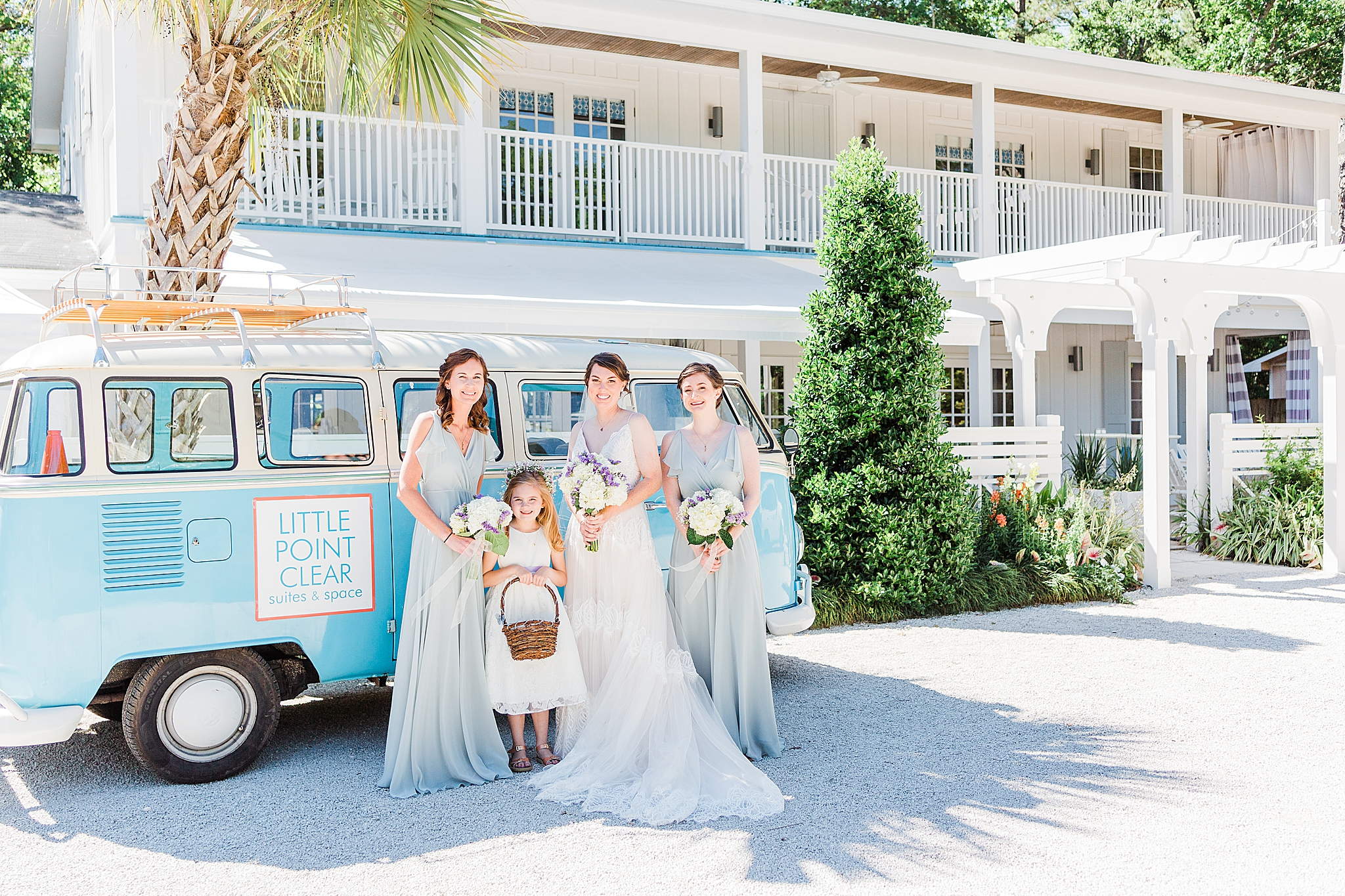 bride and bridesmaids pose by VW van