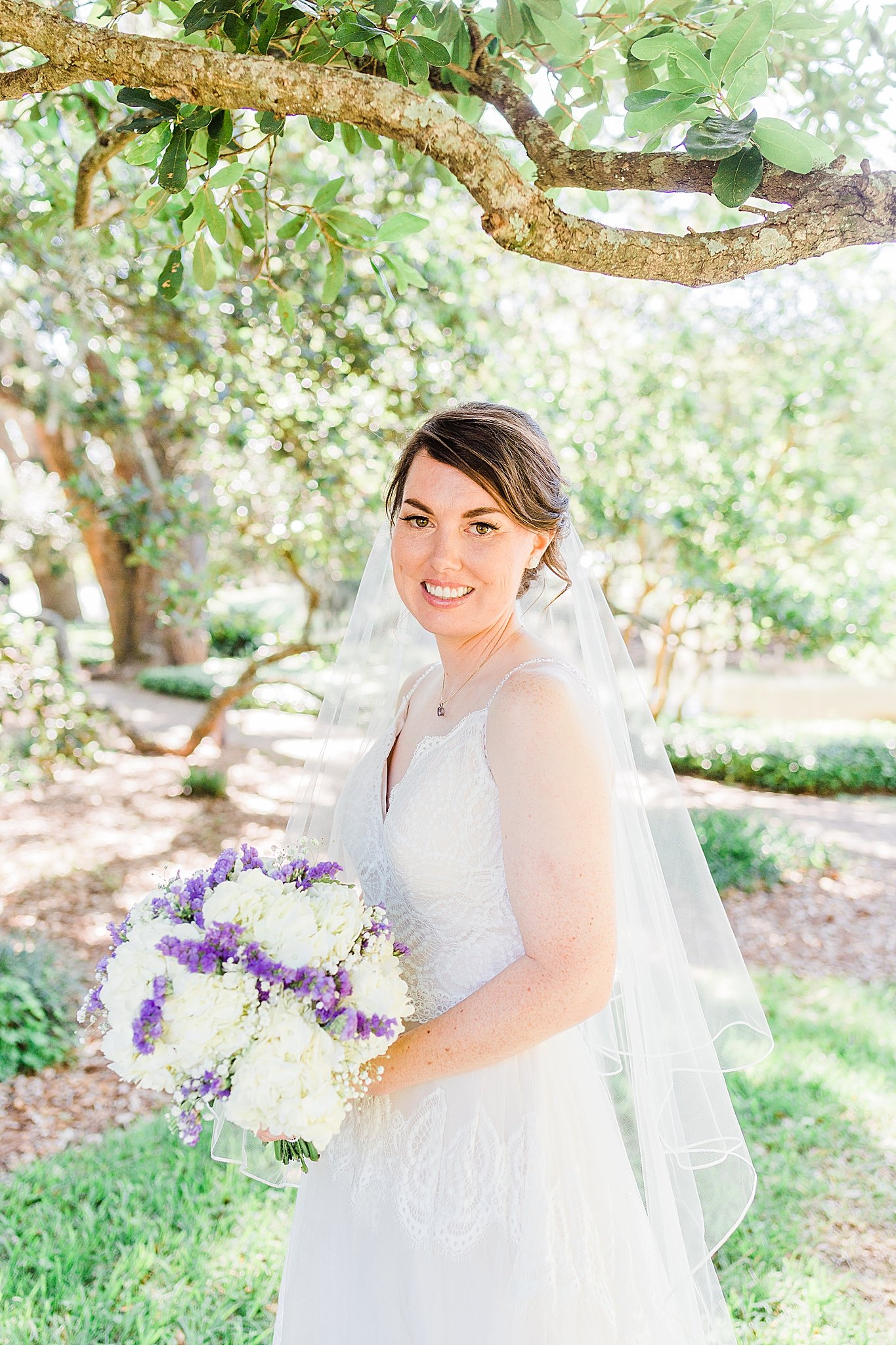 bride poses under tree in Fairhope AL