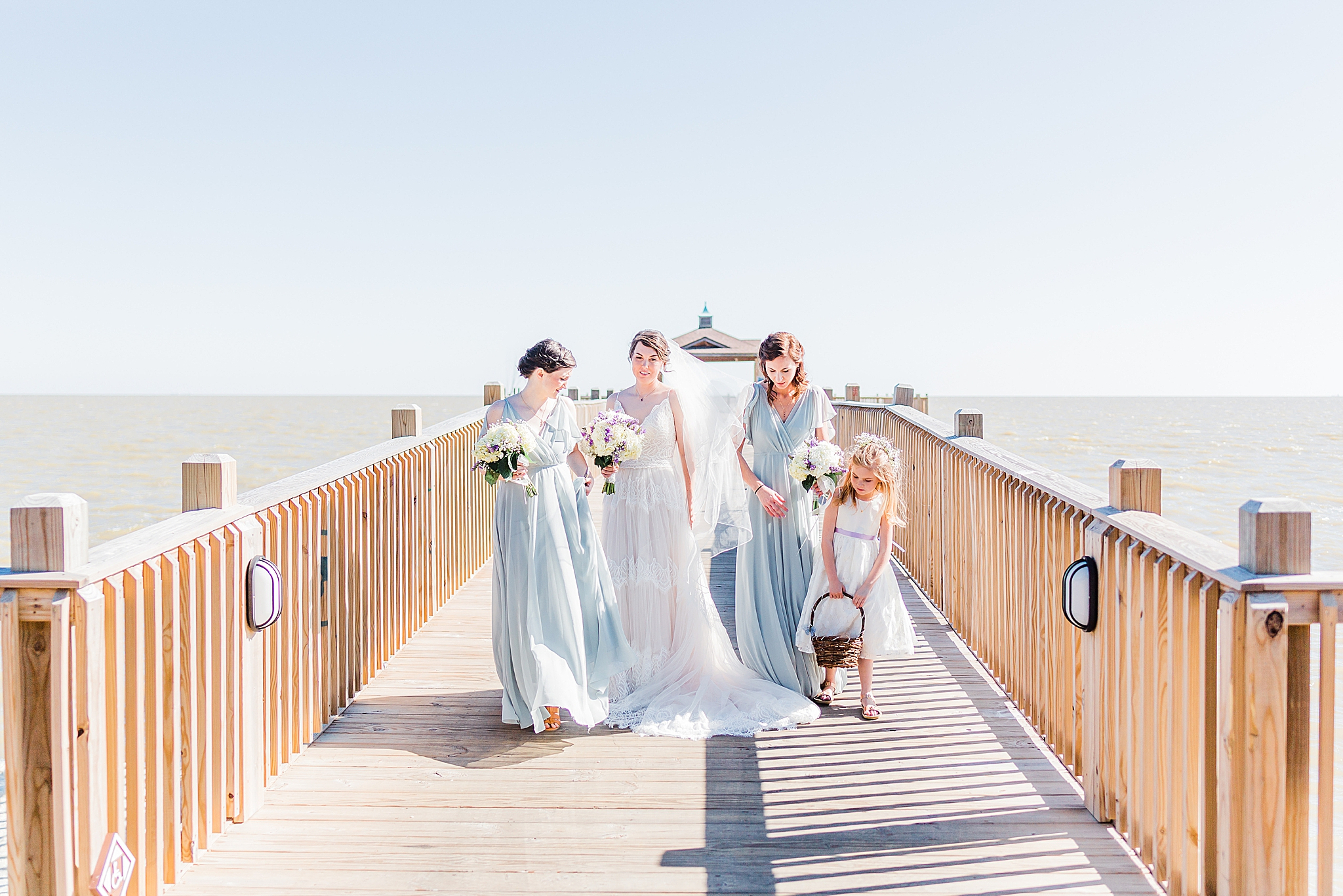 bride and bridesmaids walk on pier in Fairhope AL