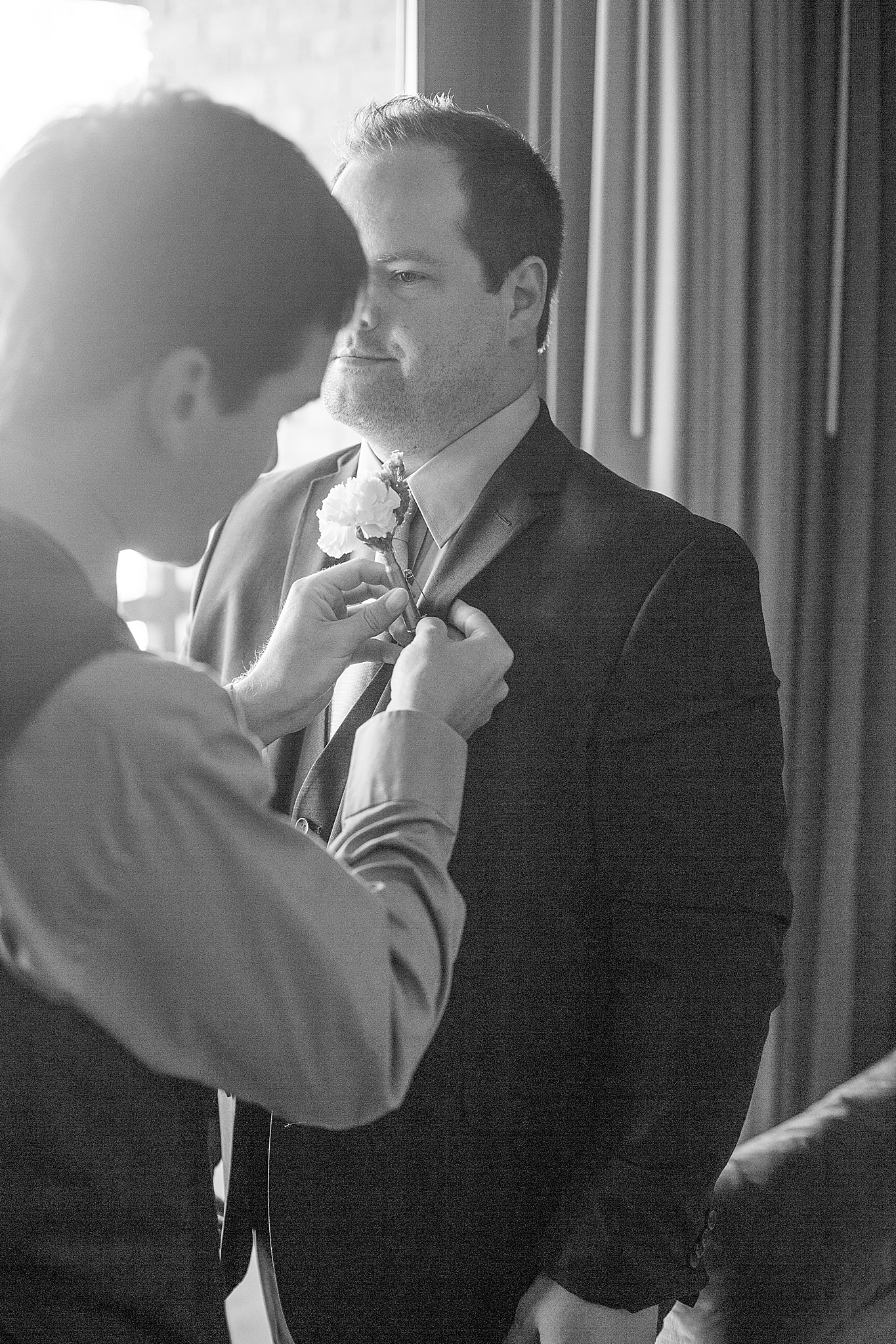 groomsman places boutonnière on groom's tux