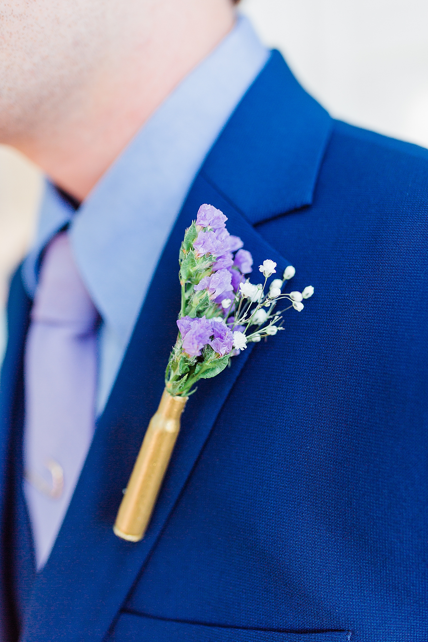 groom's purple floral boutineere on navy suit