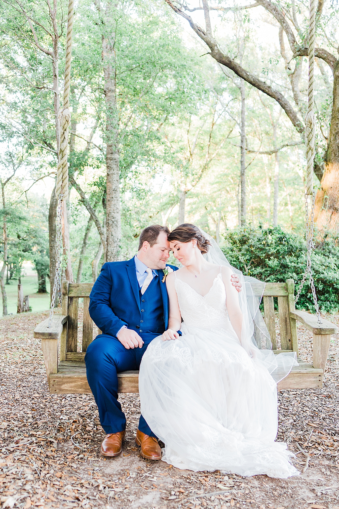 newlyweds sit on wooden bench in Fairhope AL