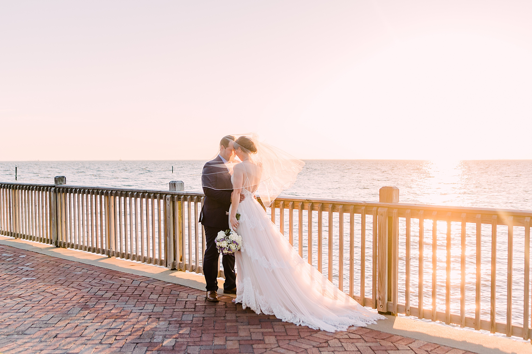 sunset wedding portraits along waterfront in Fairhope AL