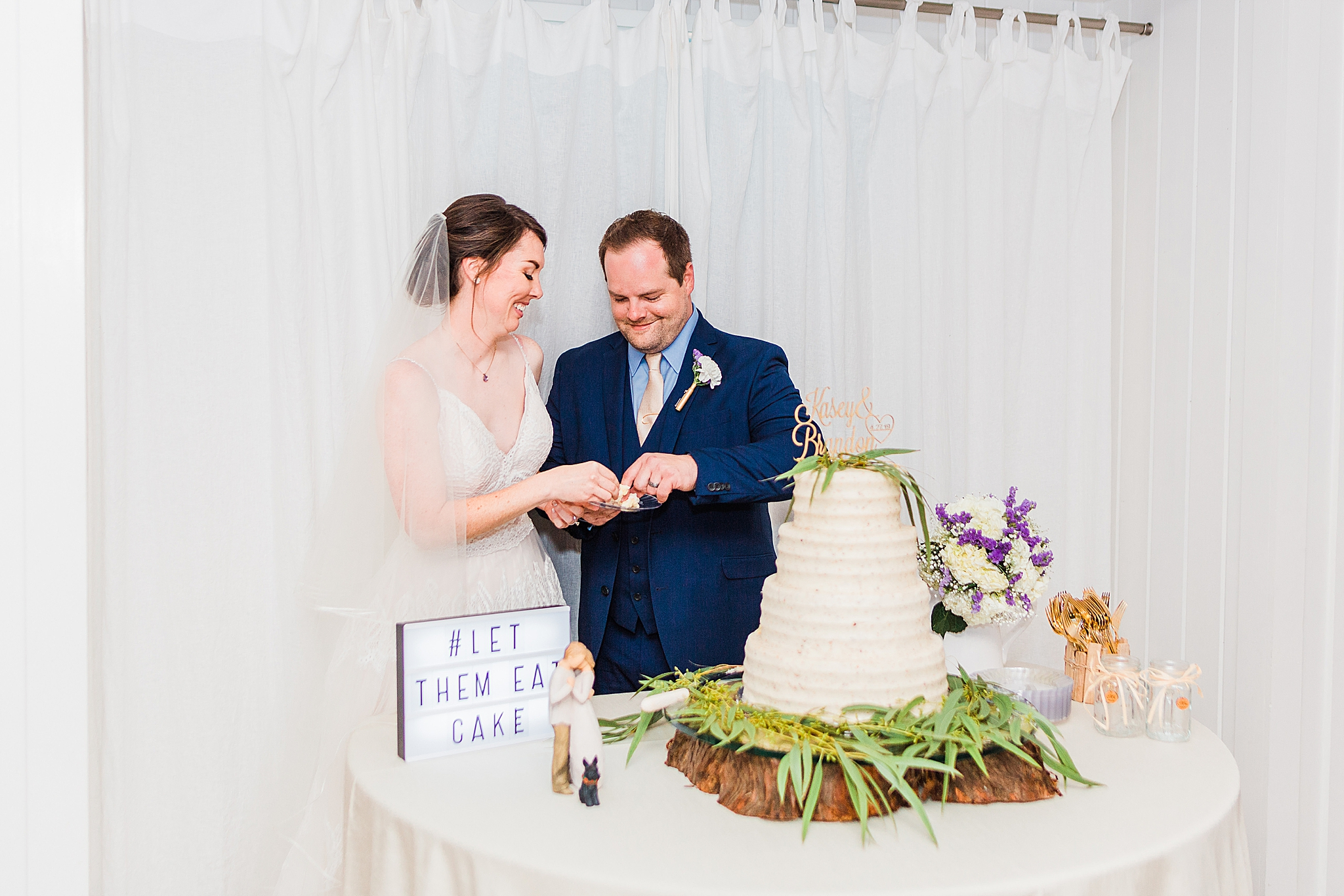 newlyweds cut wedding cake during AL wedding reception