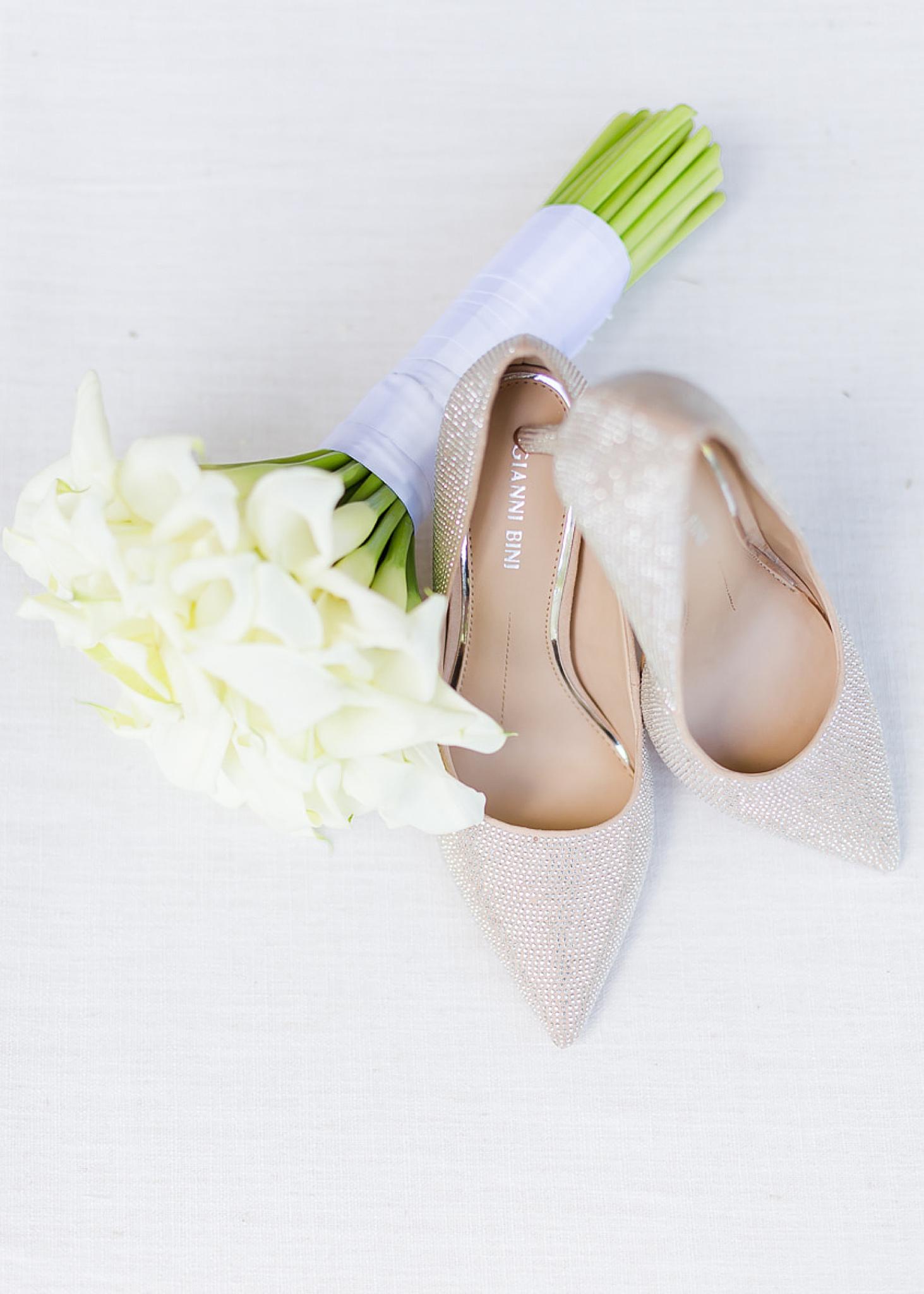 bride's pale pink shoes rest near calla lilies