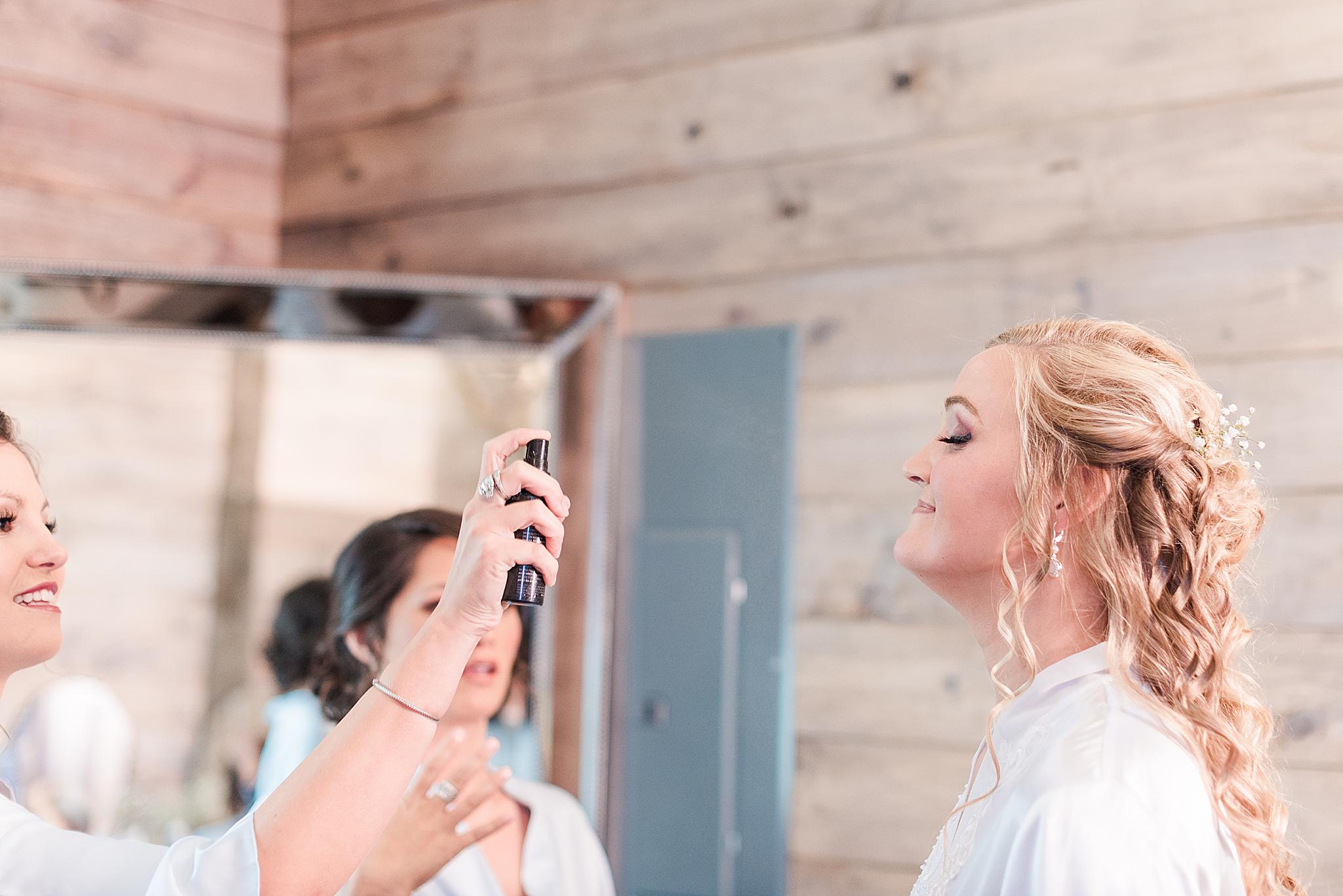 bridesmaid sprays perfume on bride for Spanish Fort AL wedding