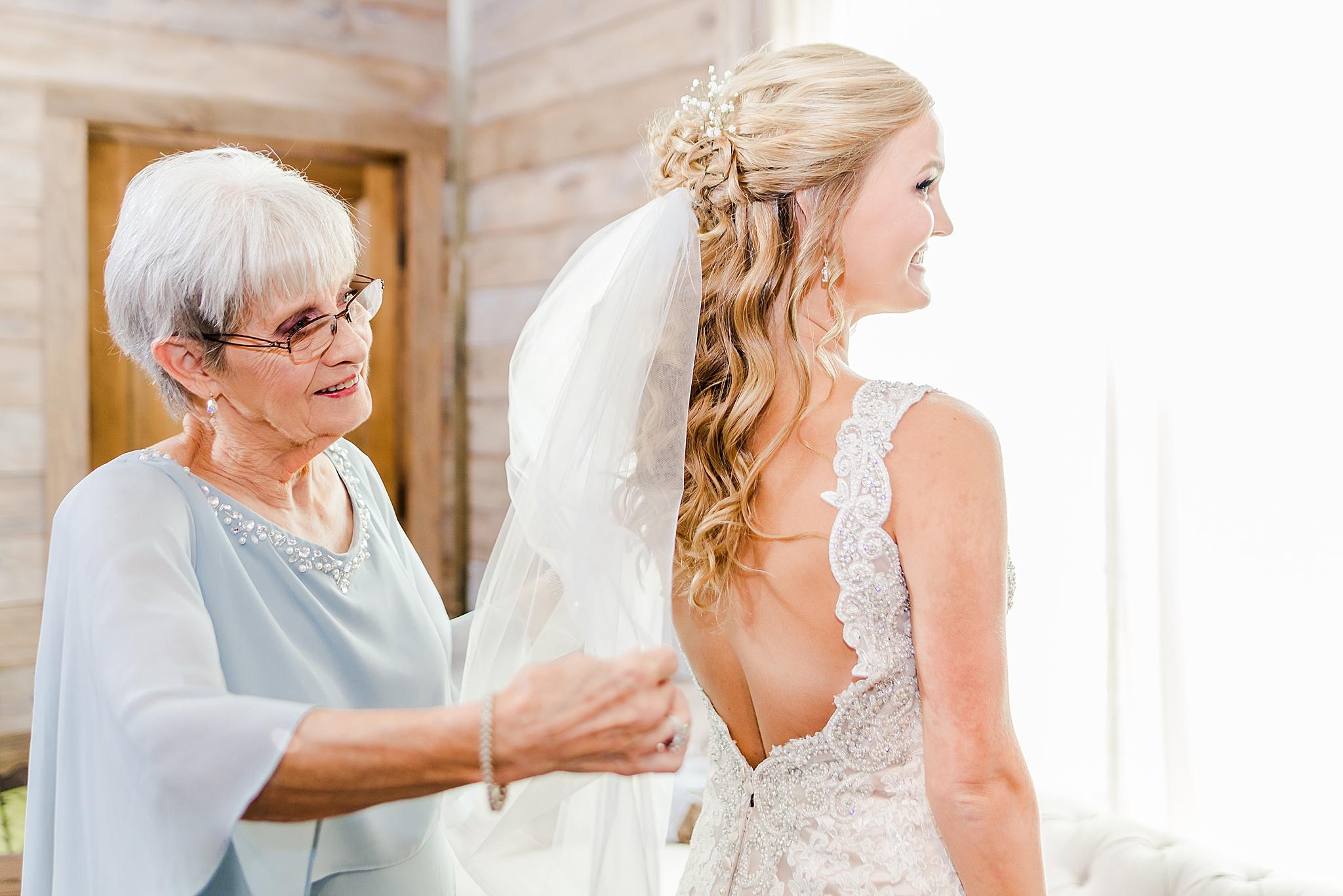 grandmother adjusts veil for bride