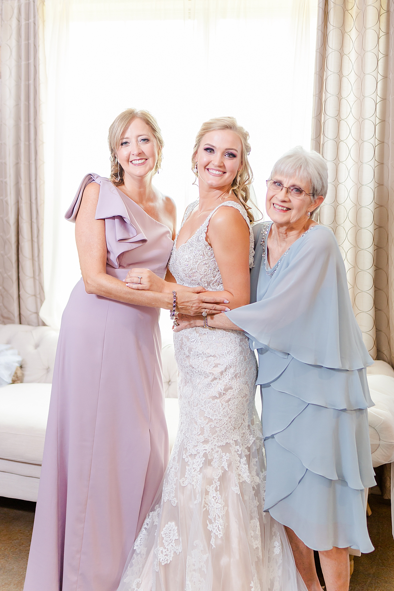 bride poses with grandmother and mother before Izenstone wedding day