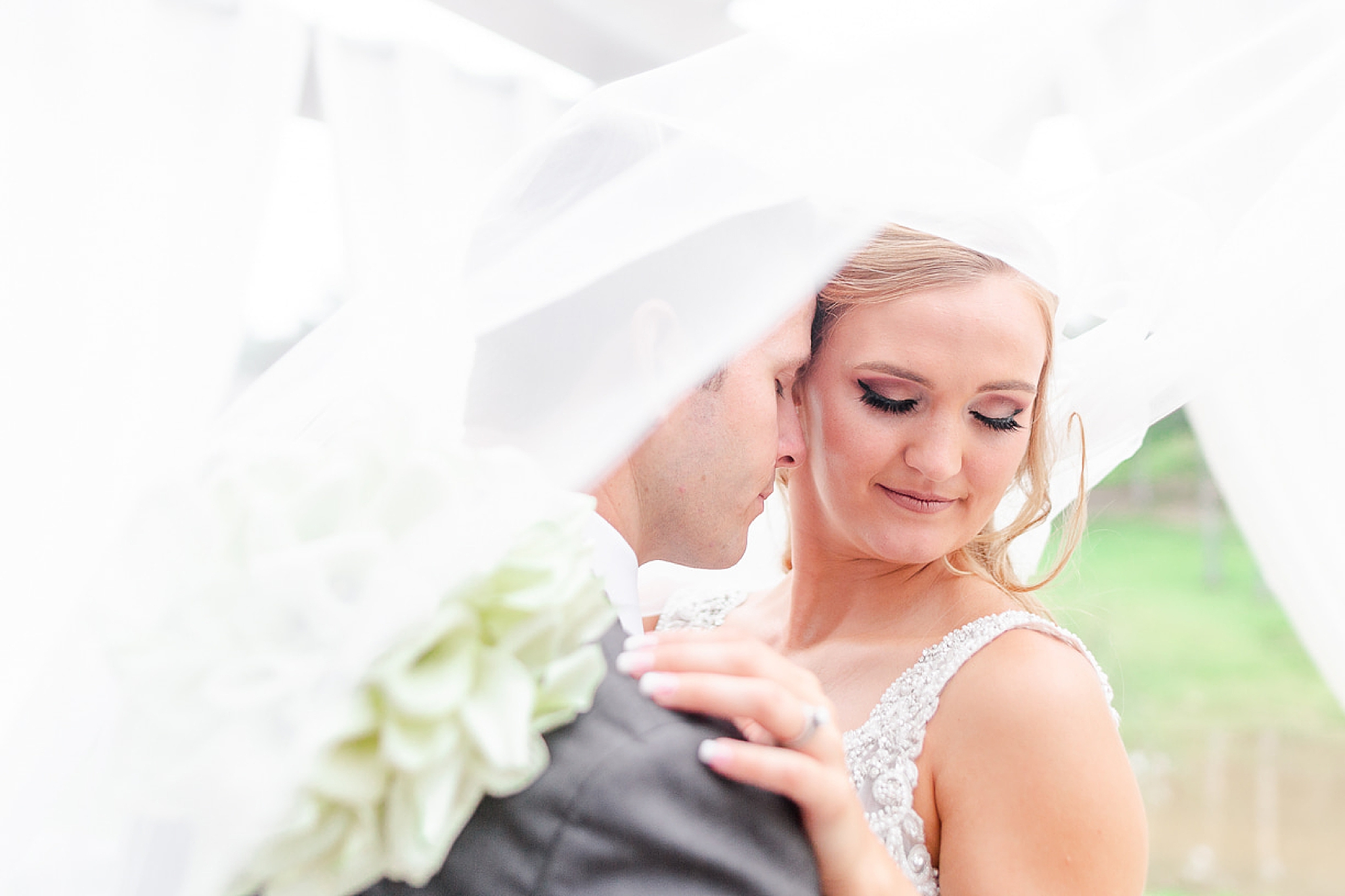 groom nuzzles bride with veil floating over them