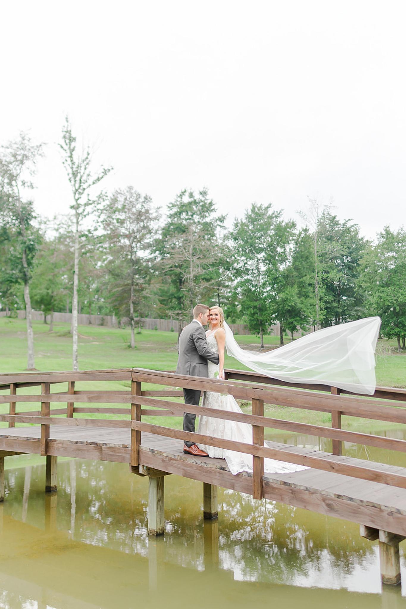bride and groom kiss on bridge during Izenstone wedding day