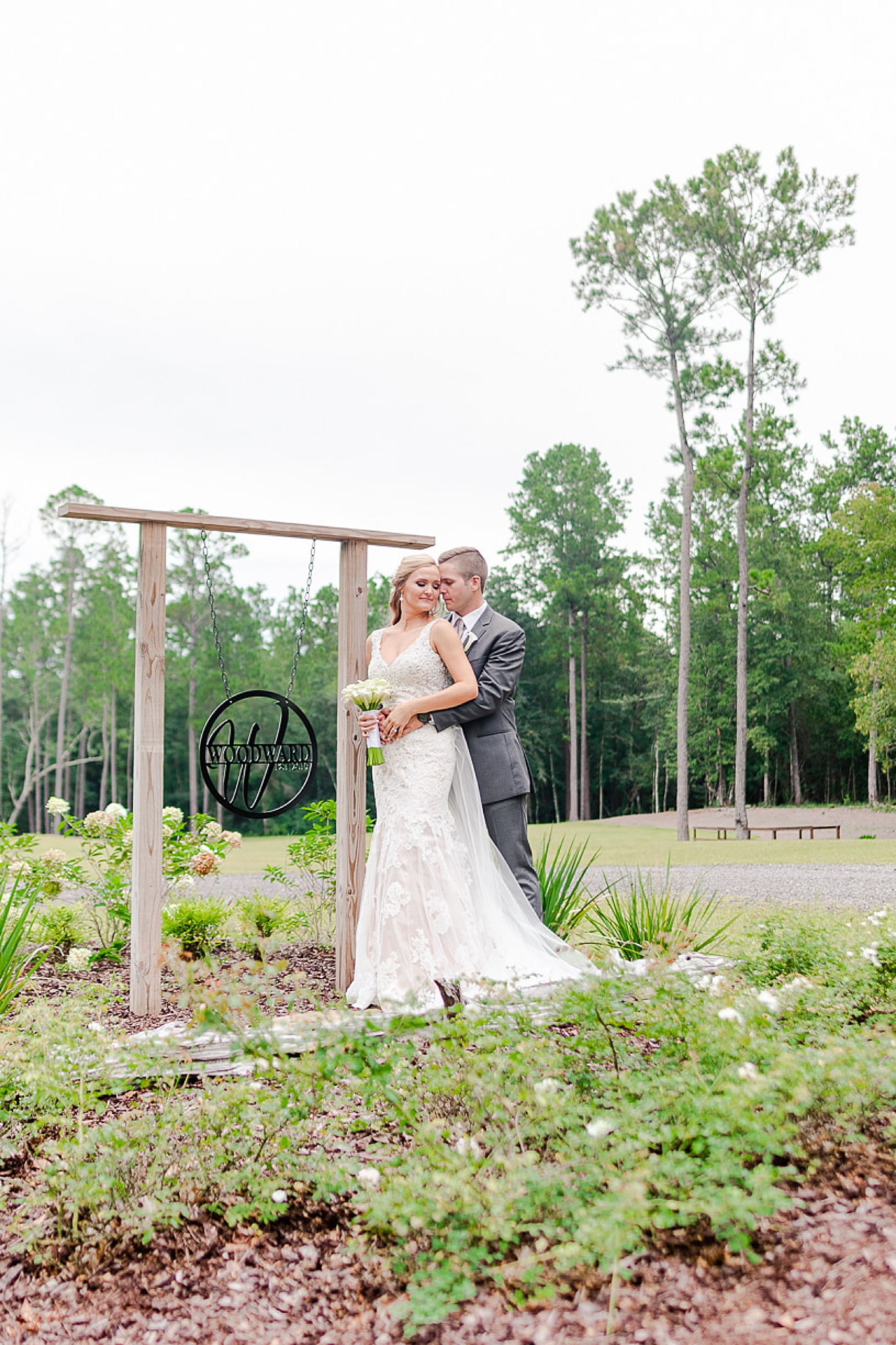 bride and groom pose by metal sign at Izenstone