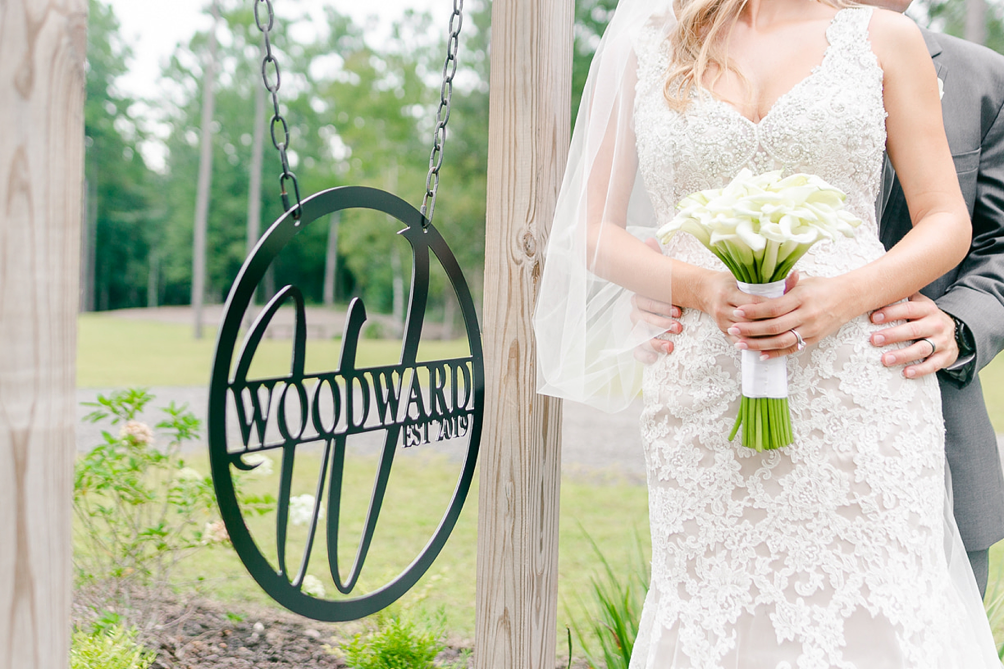 couple poses by custom sign on Izenstone wedding day