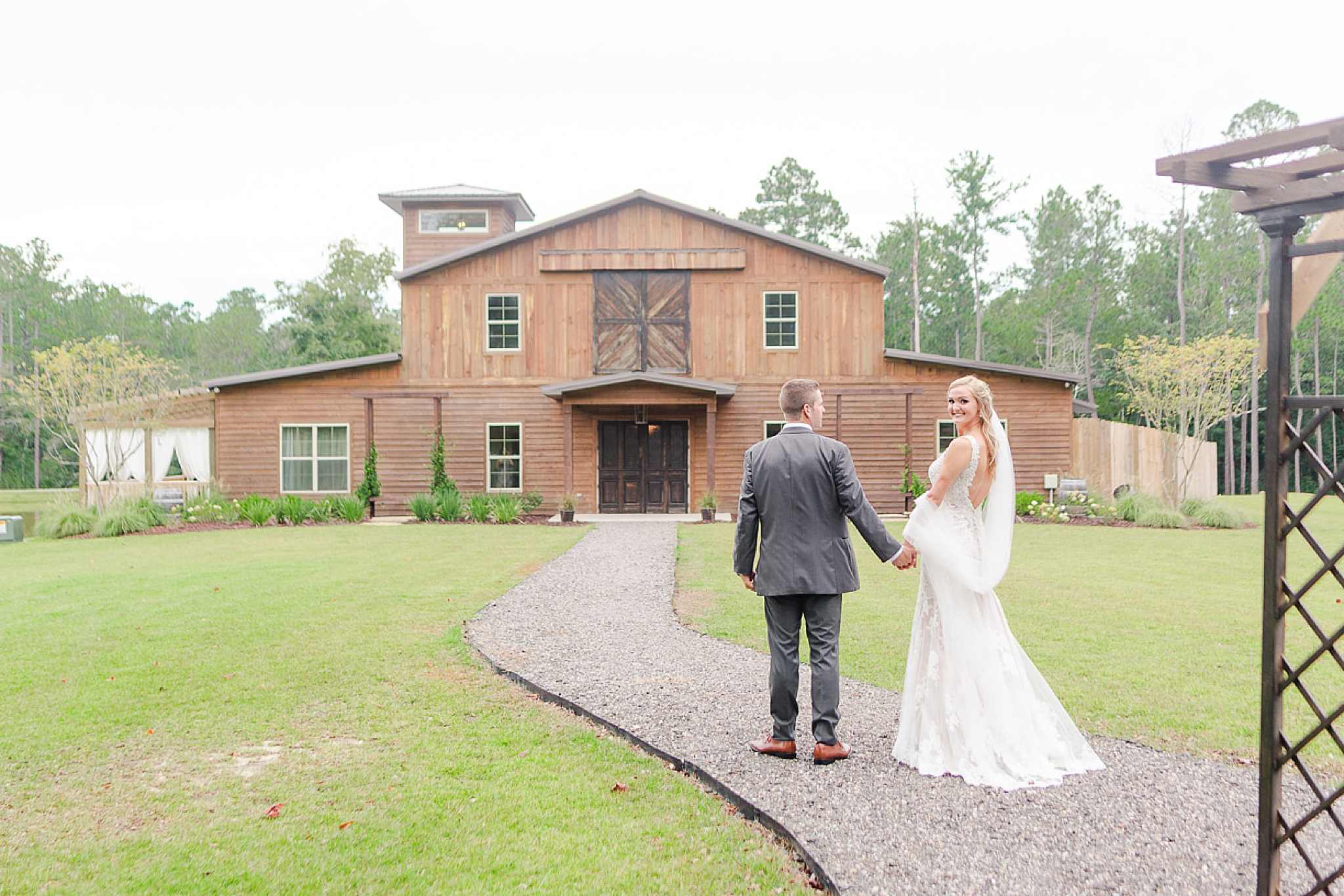 couple walks towards Izenstone on Spanish Fort AL wedding