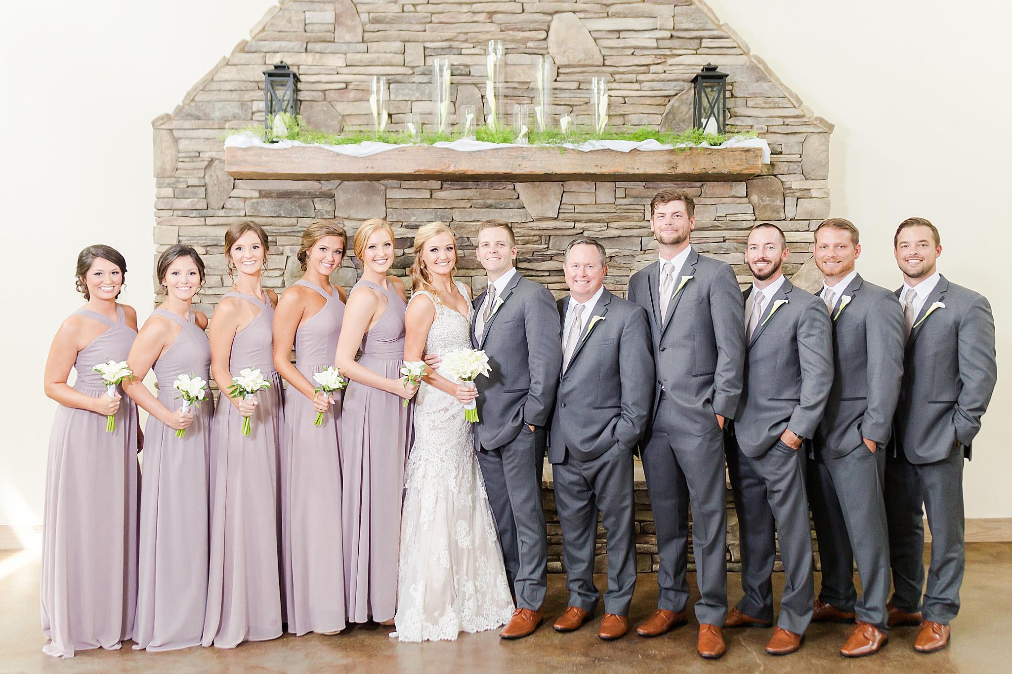bridal party poses by stone chimney at Izenstone