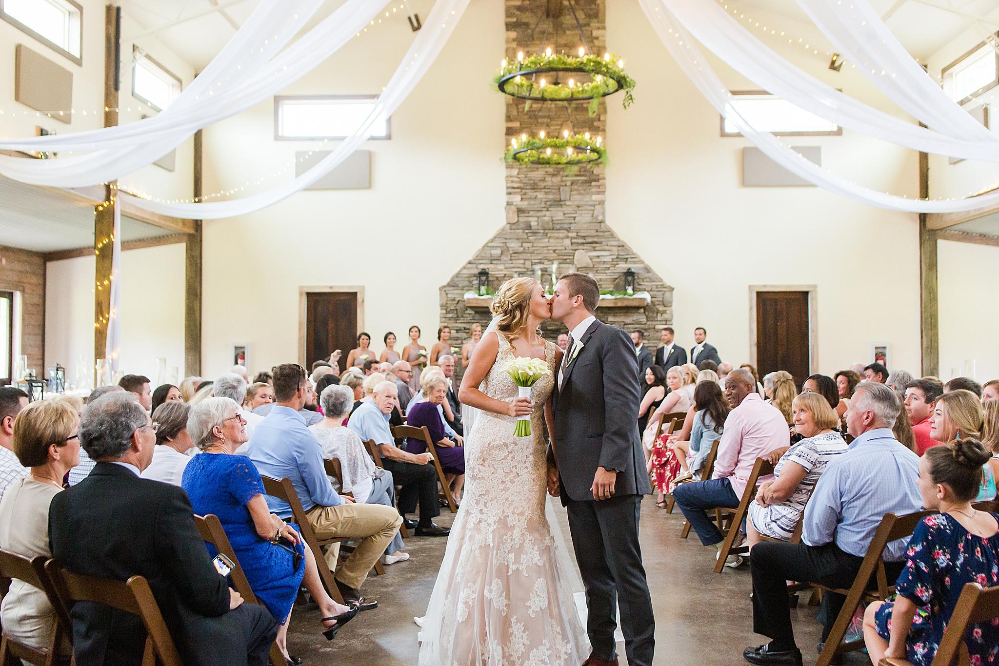 bride and groom leave wedding ceremony on Izenstone wedding day