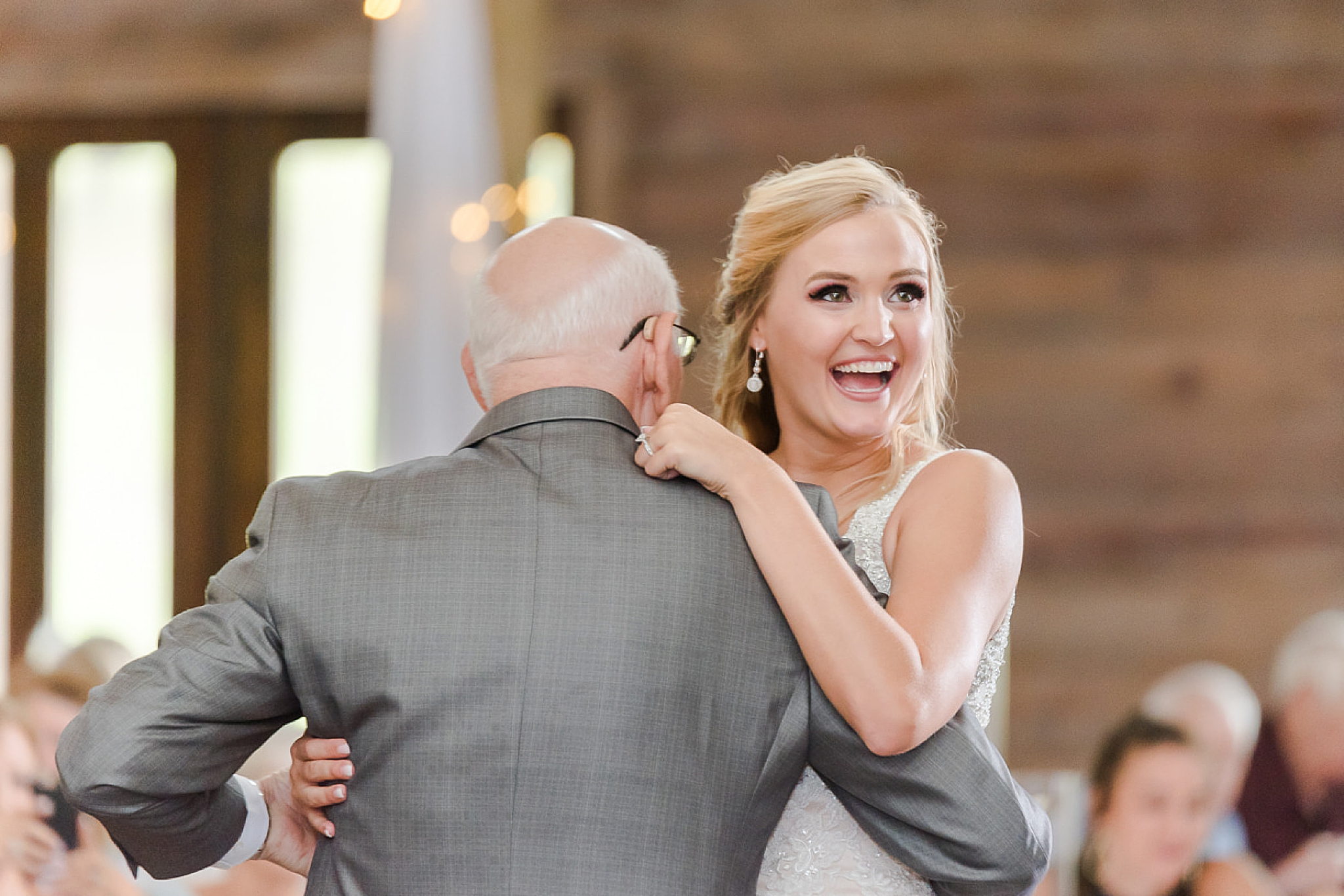 bride laughs dancing with grandfather