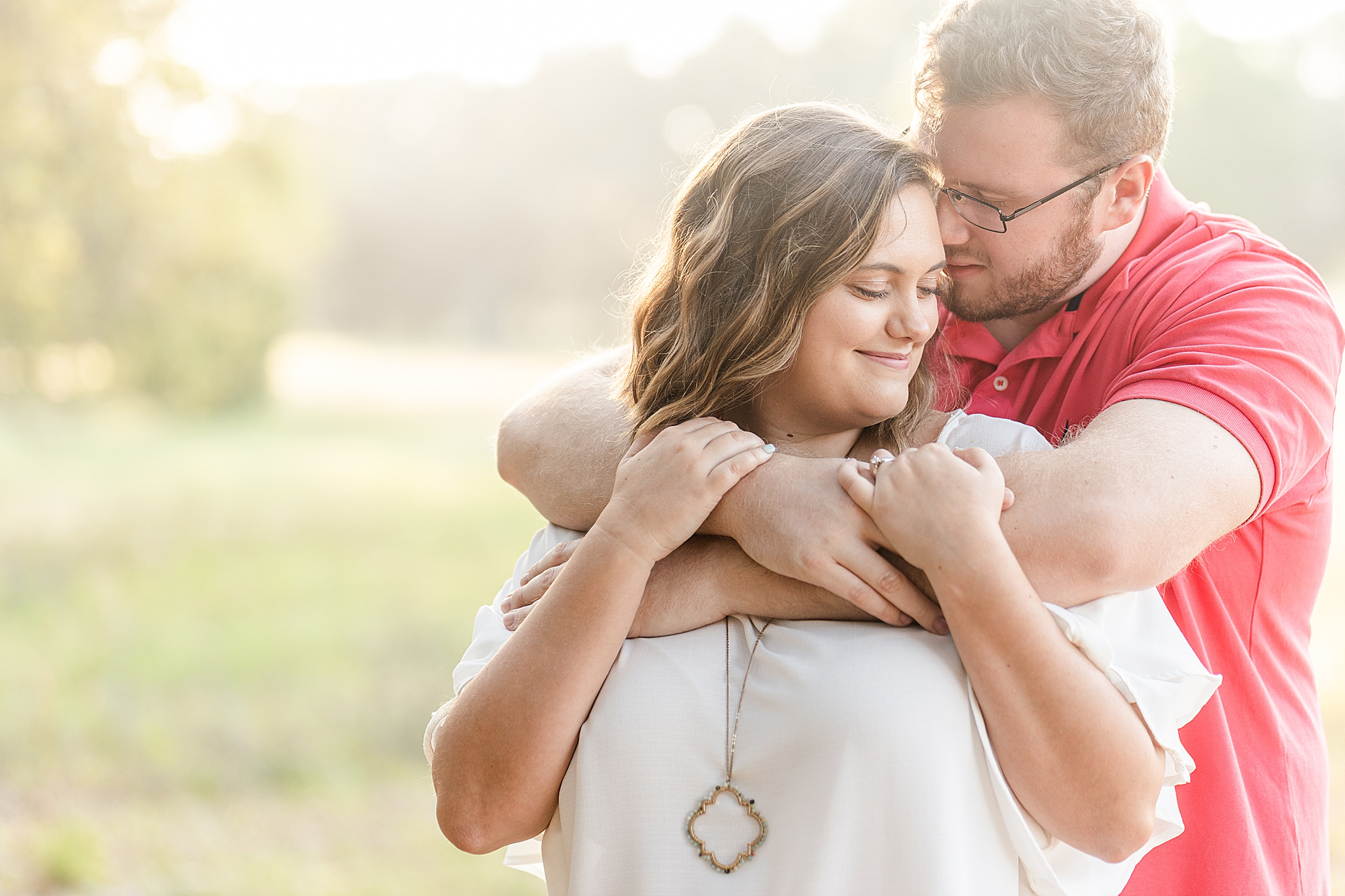groom hugs fiancee during Gulf State Park engagement session
