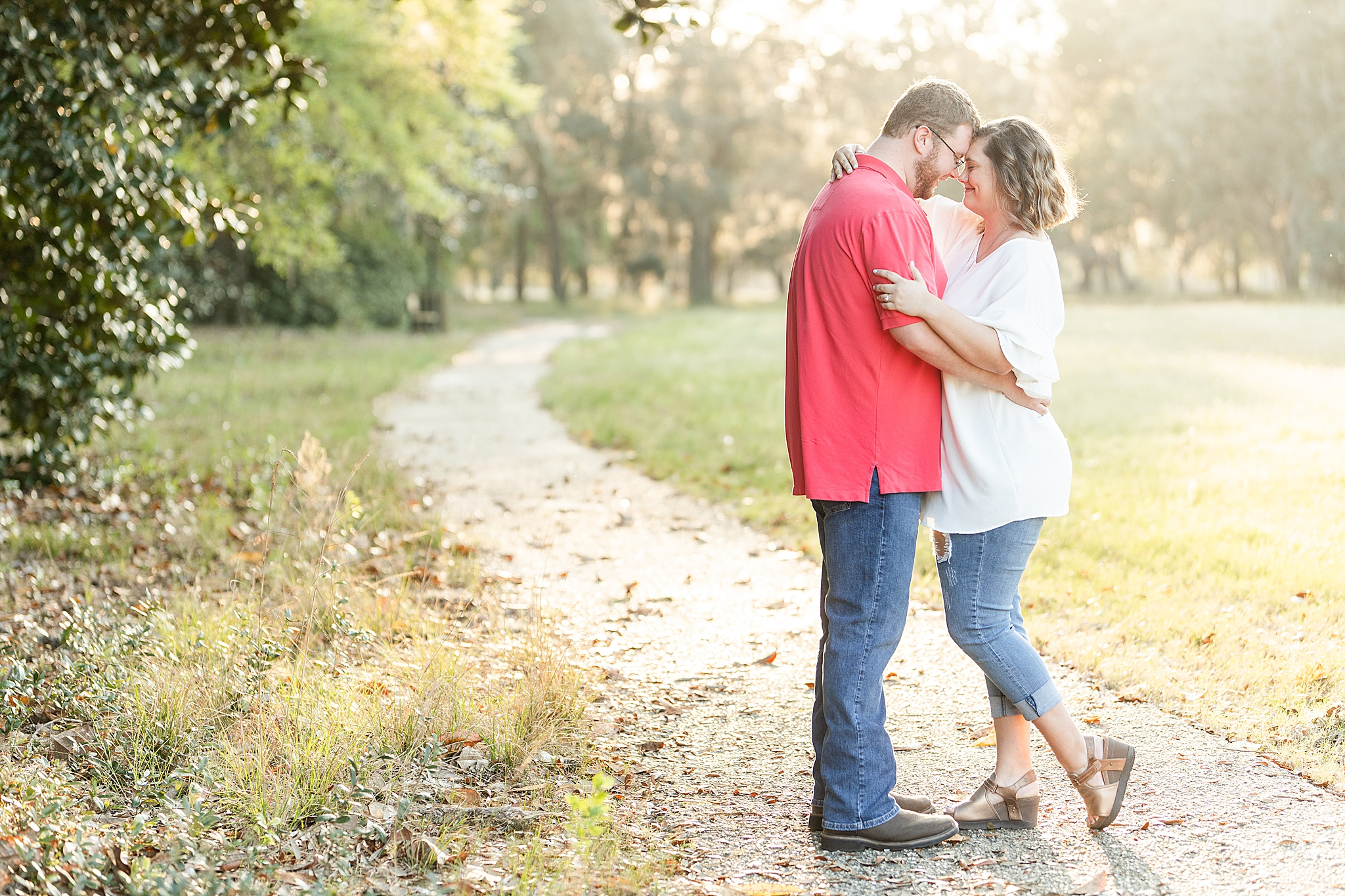 engaged couple poses touching foreheads at Gulf State Park