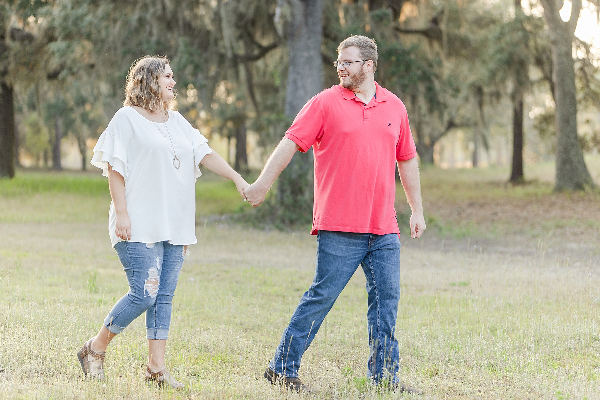 engaged couple holds hands walking through Gulf State Park