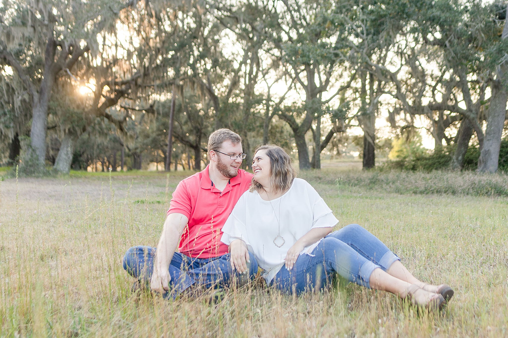couple sits in the grass at Gulf State Park