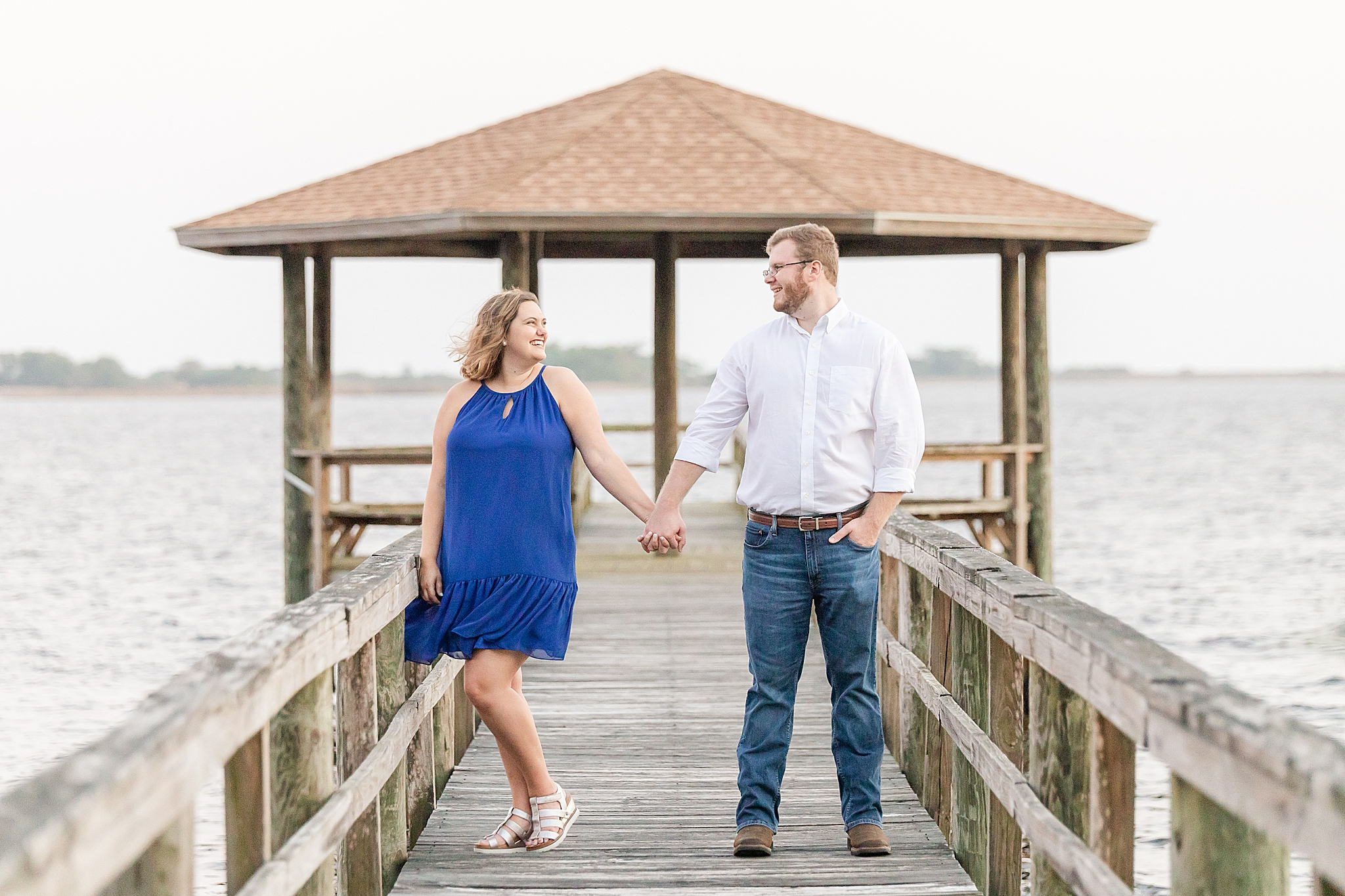 bride and groom pose on wooden walkway at Gulf State Park