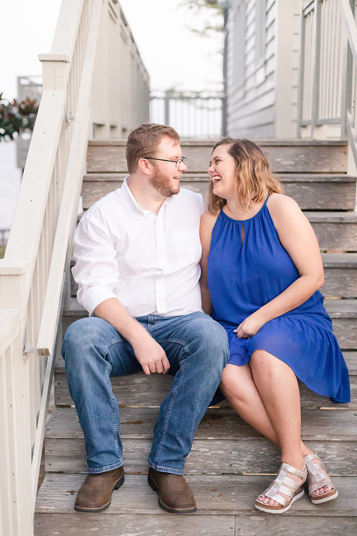 engaged couple laughs on wooden steps at Gulf State Park