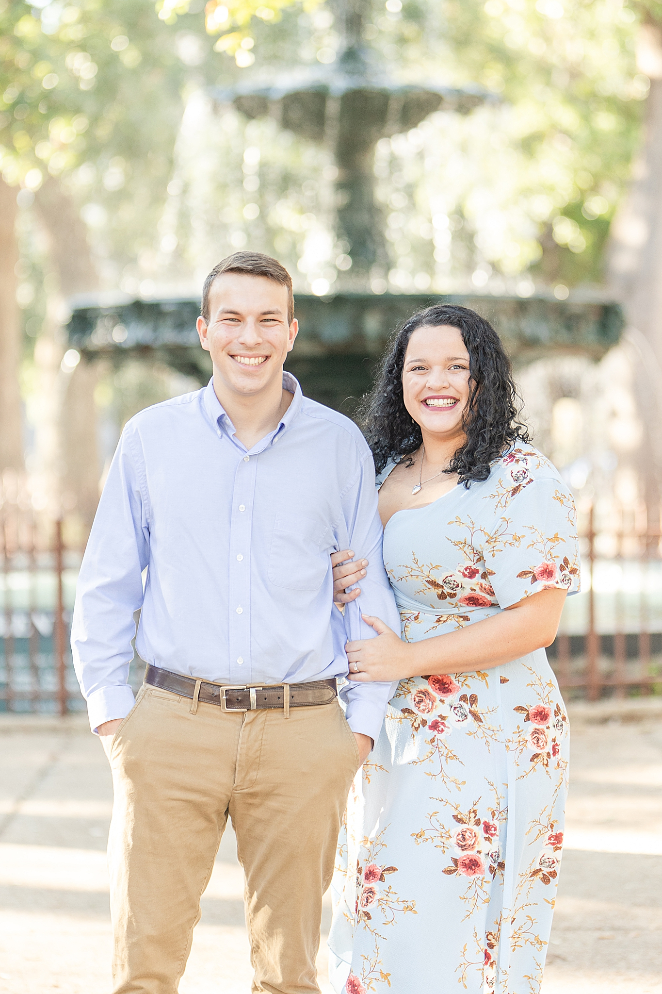 engaged couple smiles in font of Bienville Square fountain