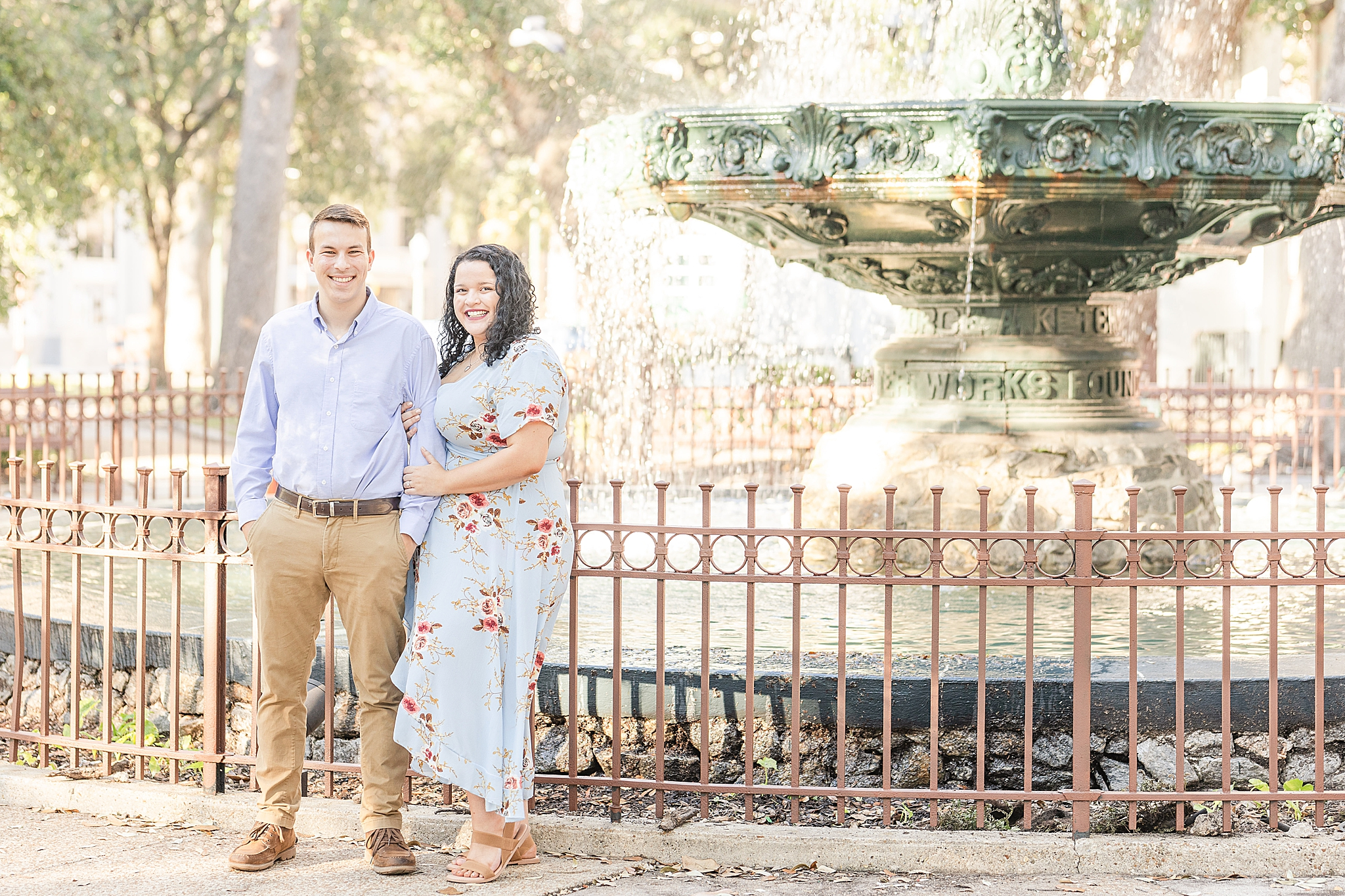couple poses by fountain in downtown Bienville Square