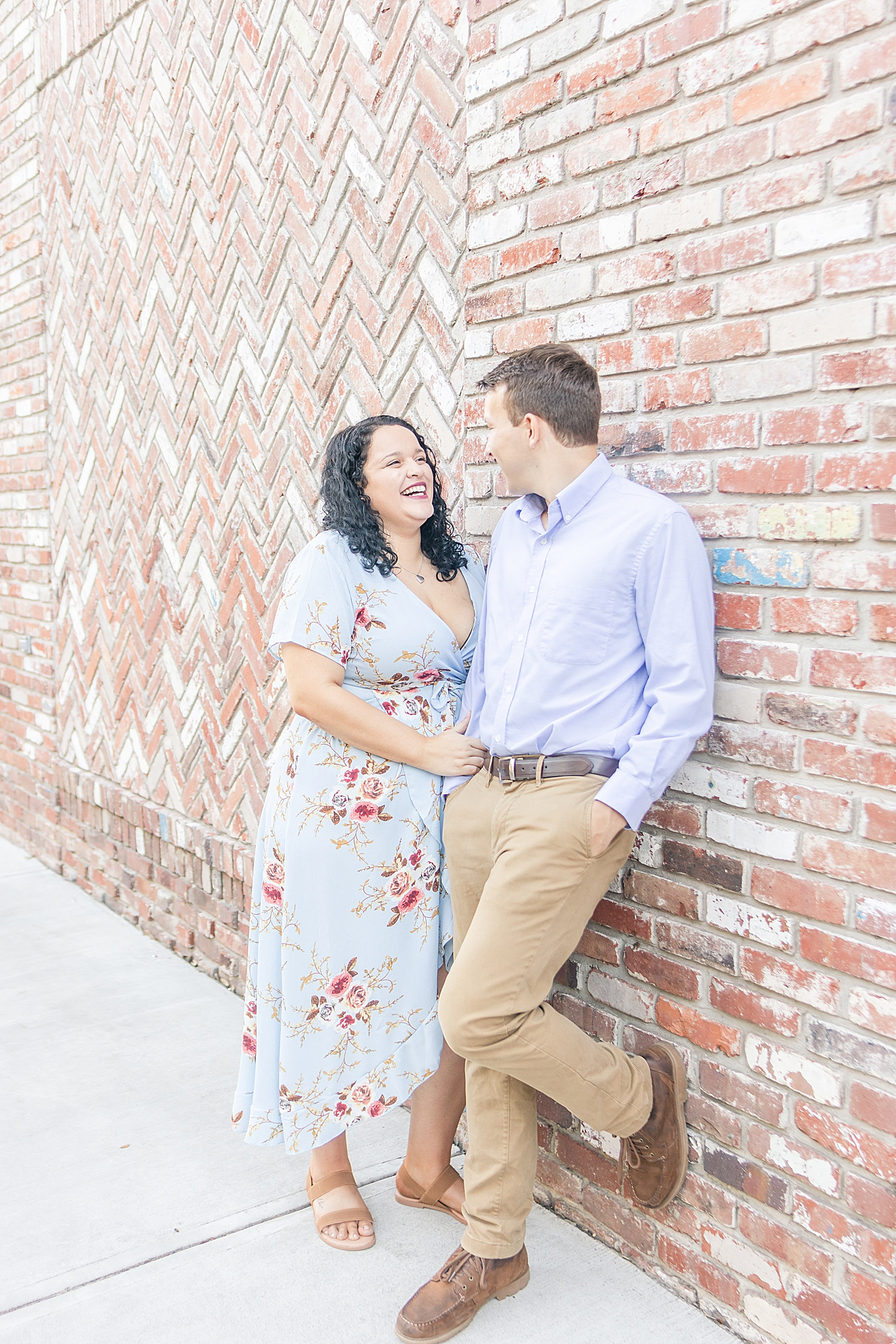 Bienville Square engagement portraits along brick wall in downtown Fairhope