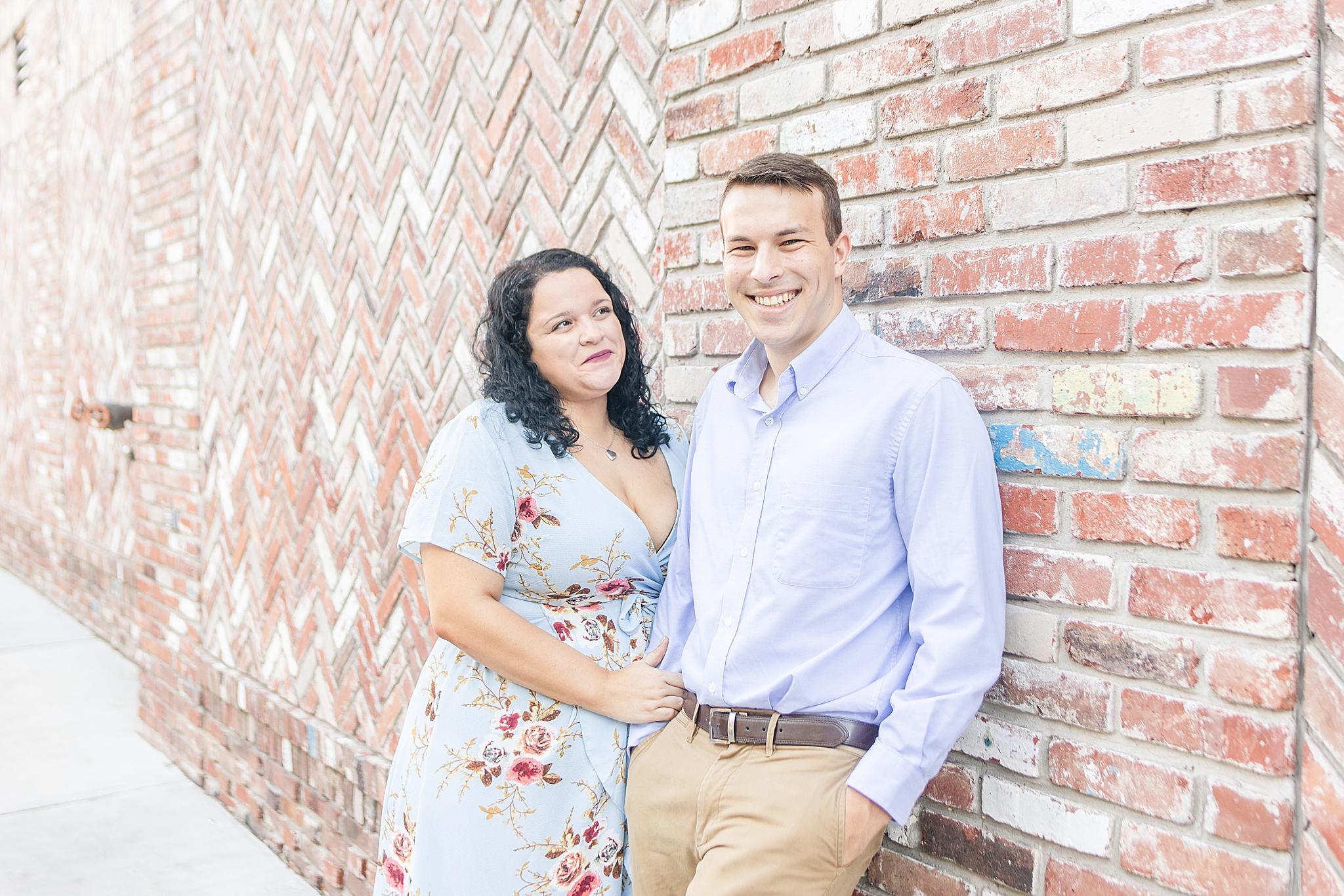 Fairhope AL engagement portraits along brick wall