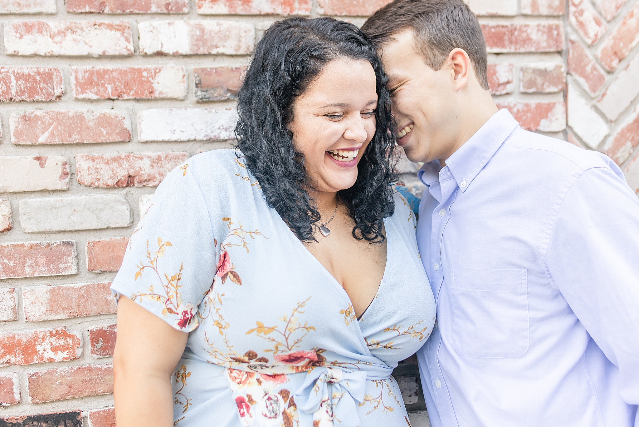 couple laughs during Alabama engagement session in Bienville Square