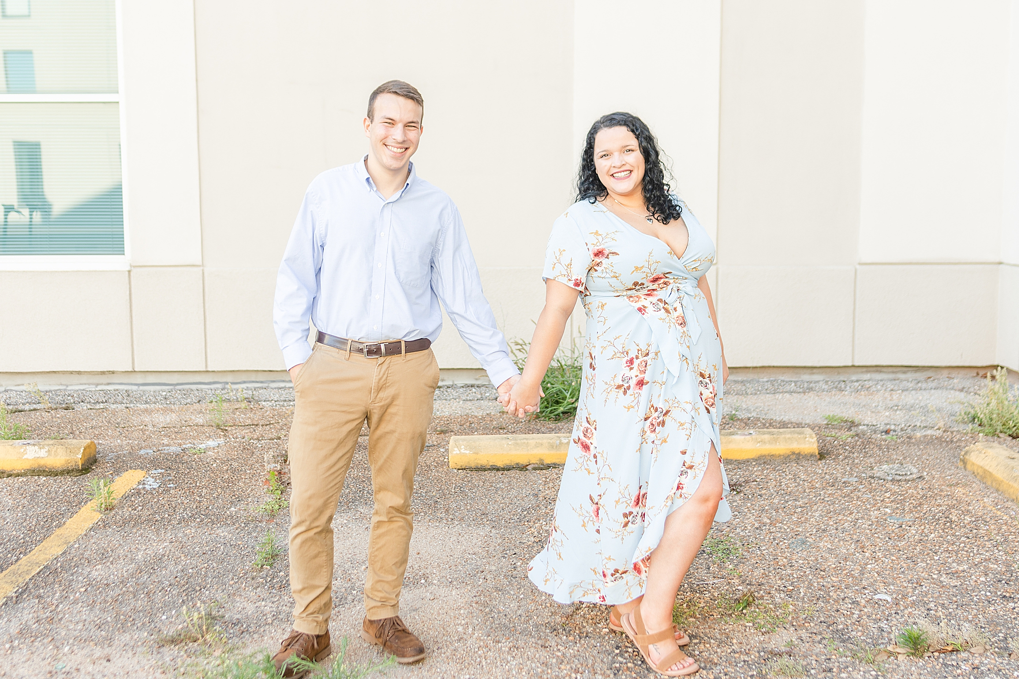 downtown Fairhope engagement portraits by white wall