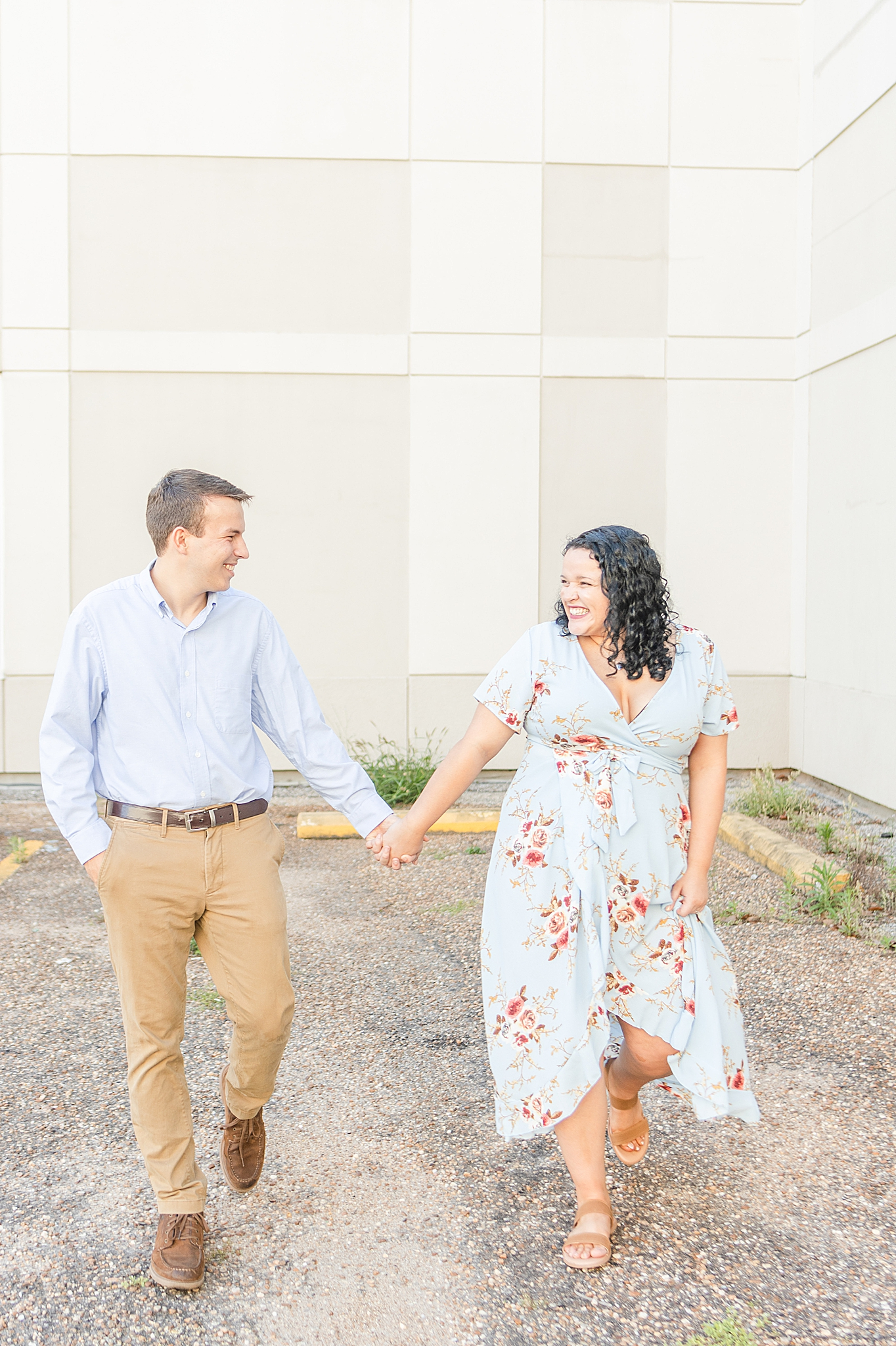 couple walks in front of white wall in Bienville Square