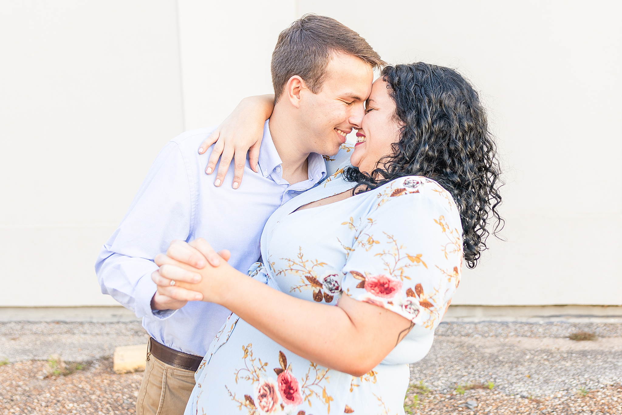 engaged couple poses nose to nose hugging