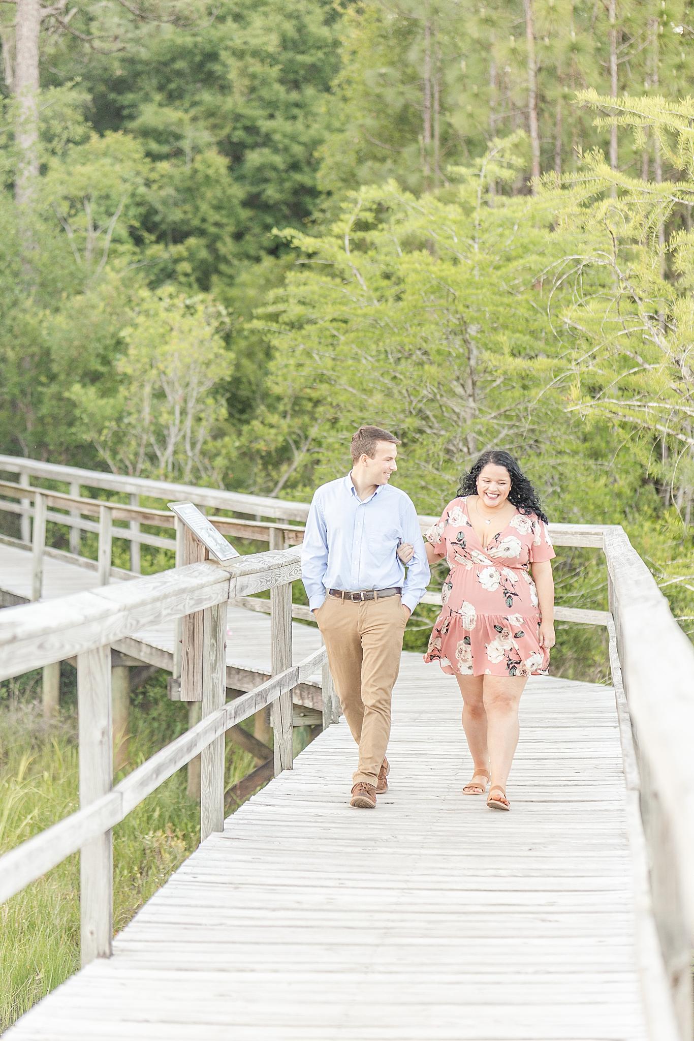couple walks on bridge in Fairhope AL during engagement photos