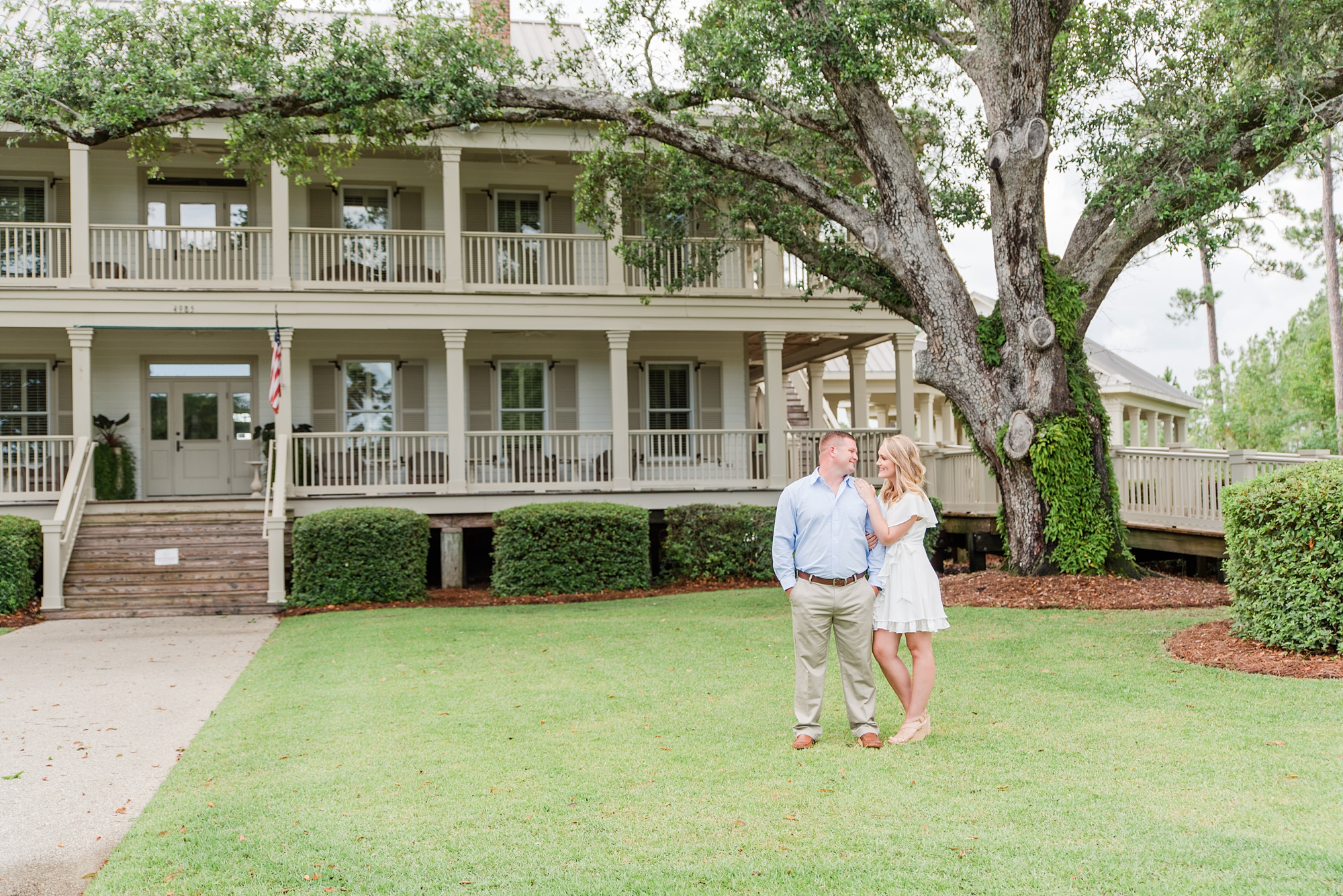 couple poses in front of home during Wharf at Orange Beach engagement photos