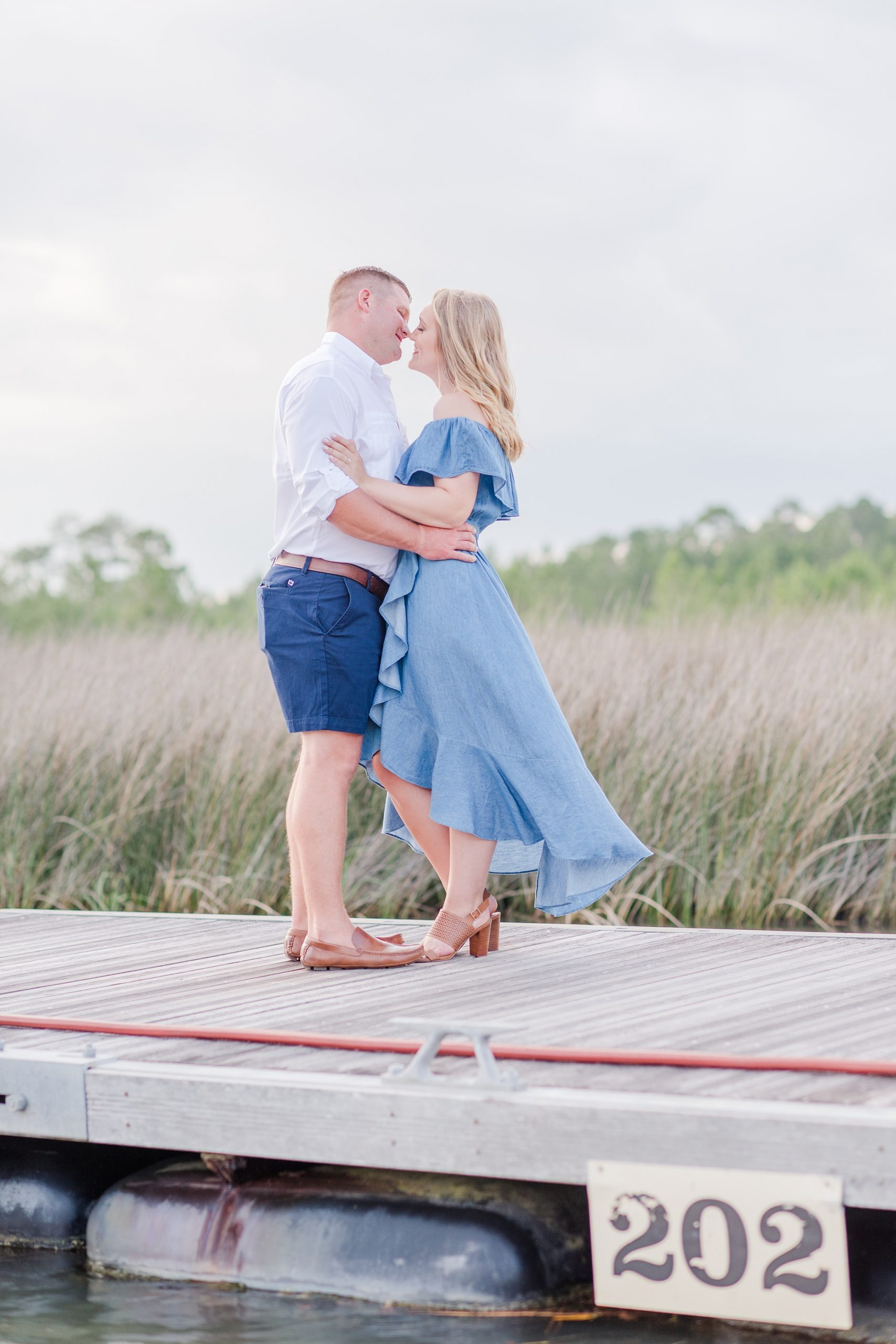 Wharf at Orange Beach engagement photos of couple kissing on dock