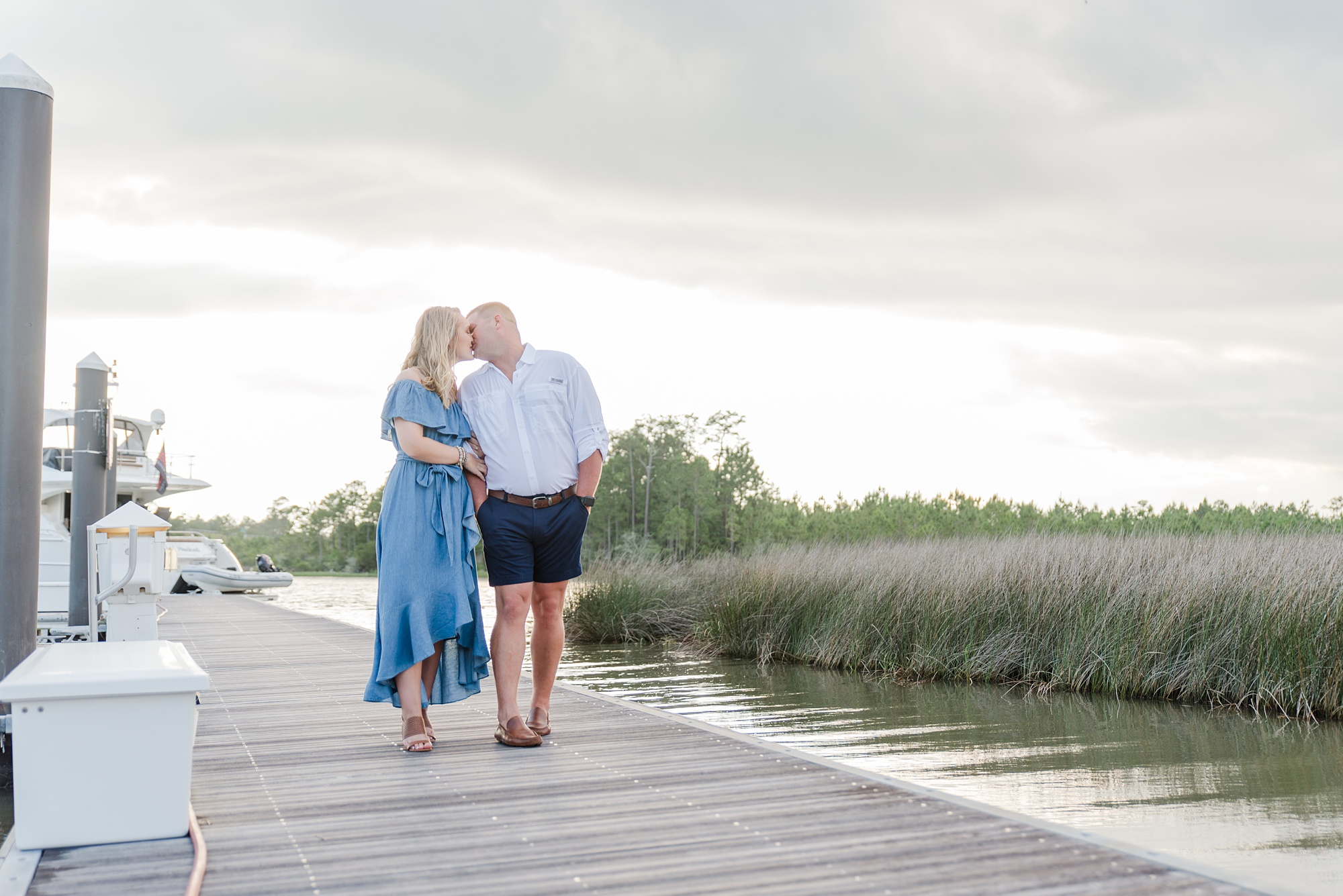 bride and groom walk along dock while storm rolls in