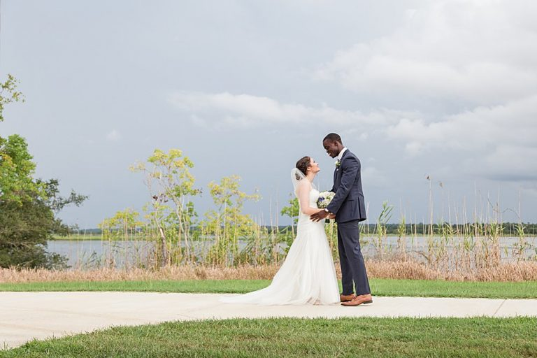 bride and groom meet during first look along Mobile Bay on rainy wedding day photographed by luxury wedding photographers Goodie and Smith Weddings