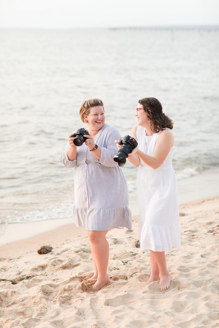 Alabama wedding photographers Goodie and Smith Weddings walk in sand along Gulf Coast with cameras