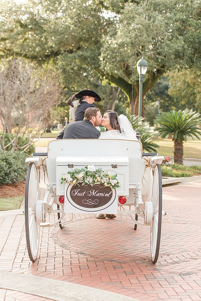 Bride and groom leaving their wedding in a horse drawn carriage at the Grand Hotel in Point Clear, Alabama