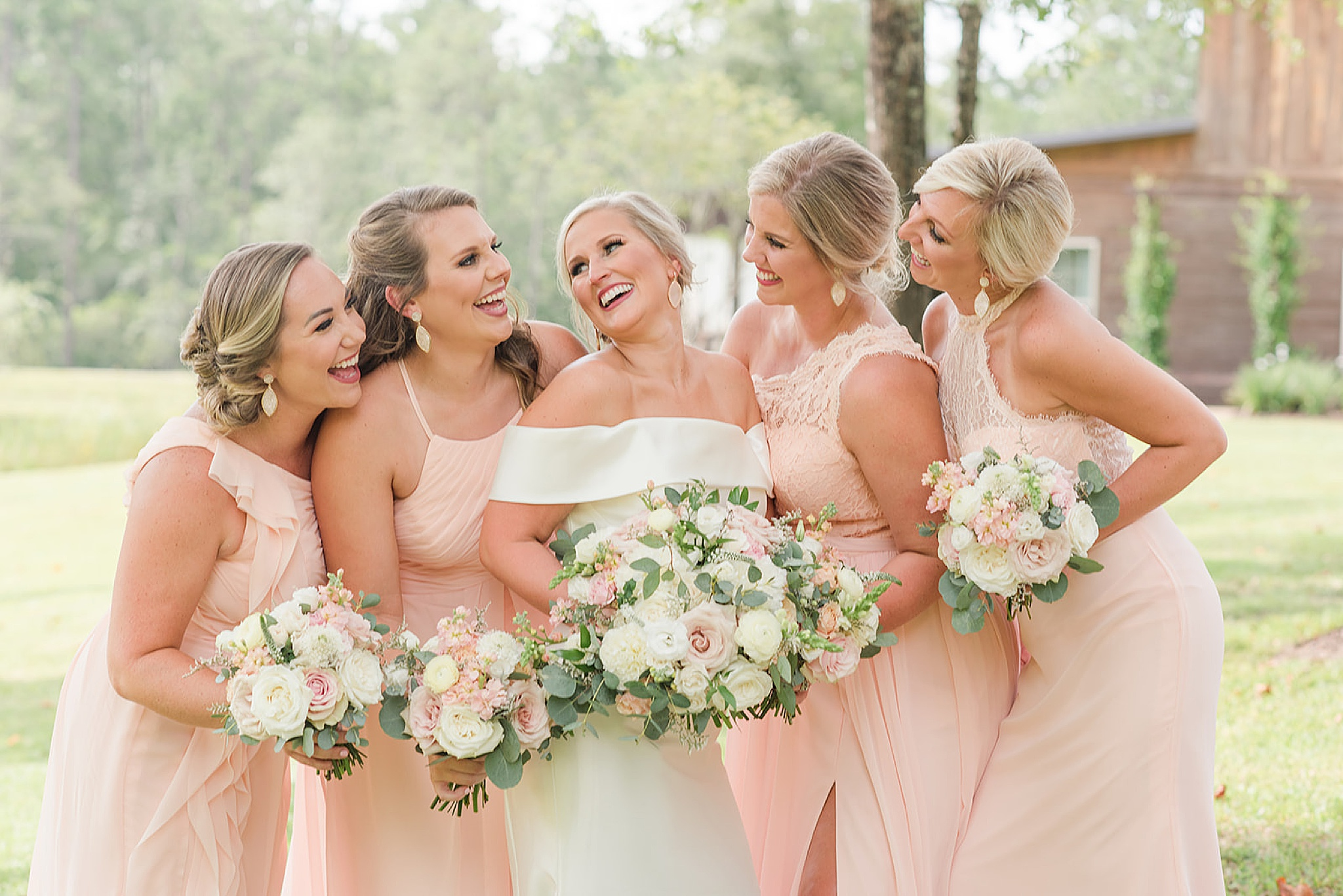 bridesmaid laughs with bridesmaids before wedding ceremony