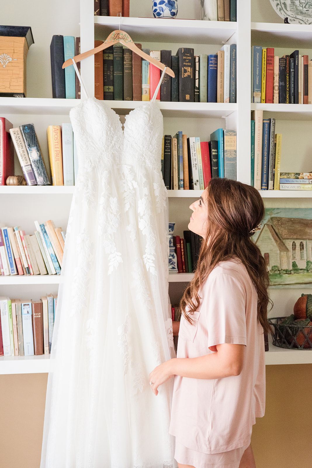 bride looks at wedding gown before putting it on