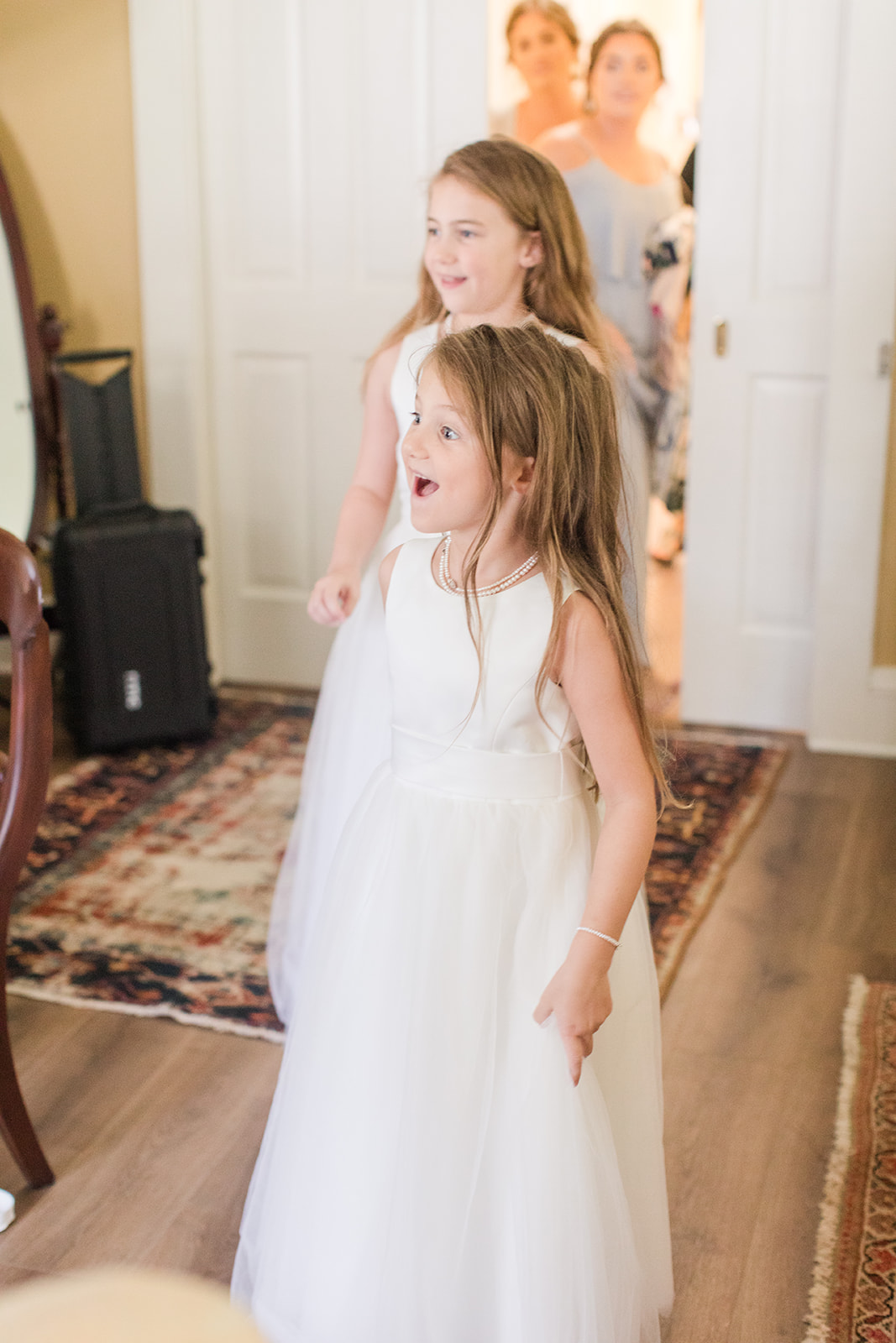 flower girl reacts to seeing bride in St. Francis at the Point sitting room