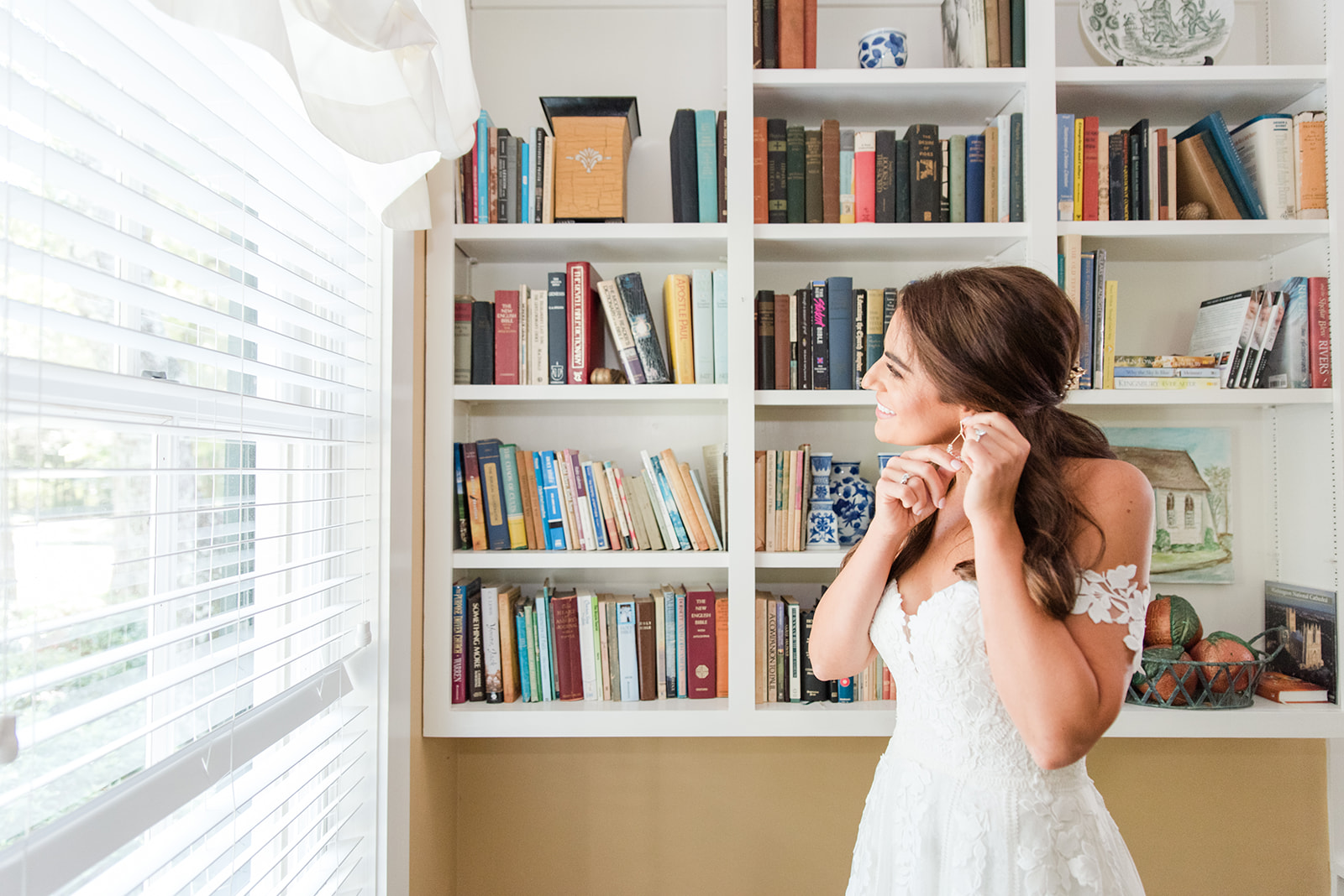 bride puts on earrings before St. Francis at the Point wedding ceremony