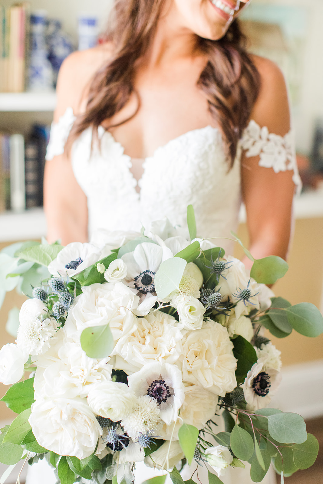 bride holds bouquet of white and green flowers