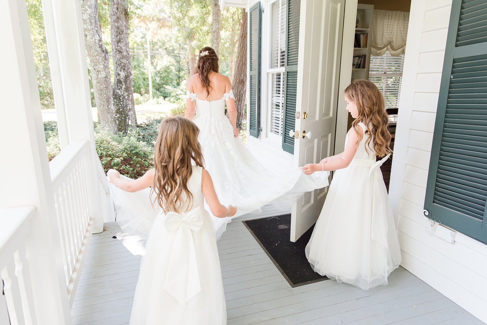 flower girls hold bride's train for first look