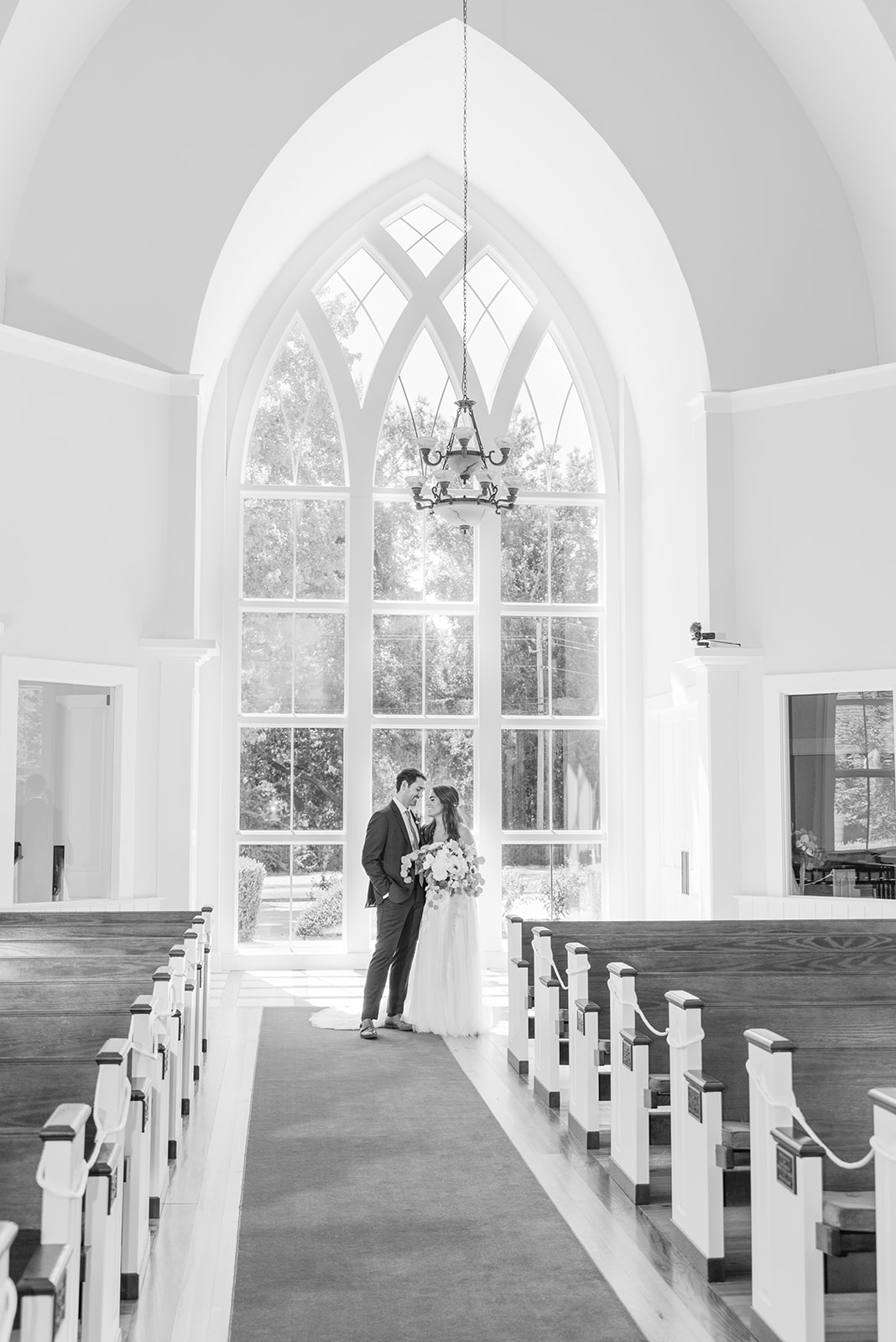 bride and groom pose by large window at St. Francis at the Point